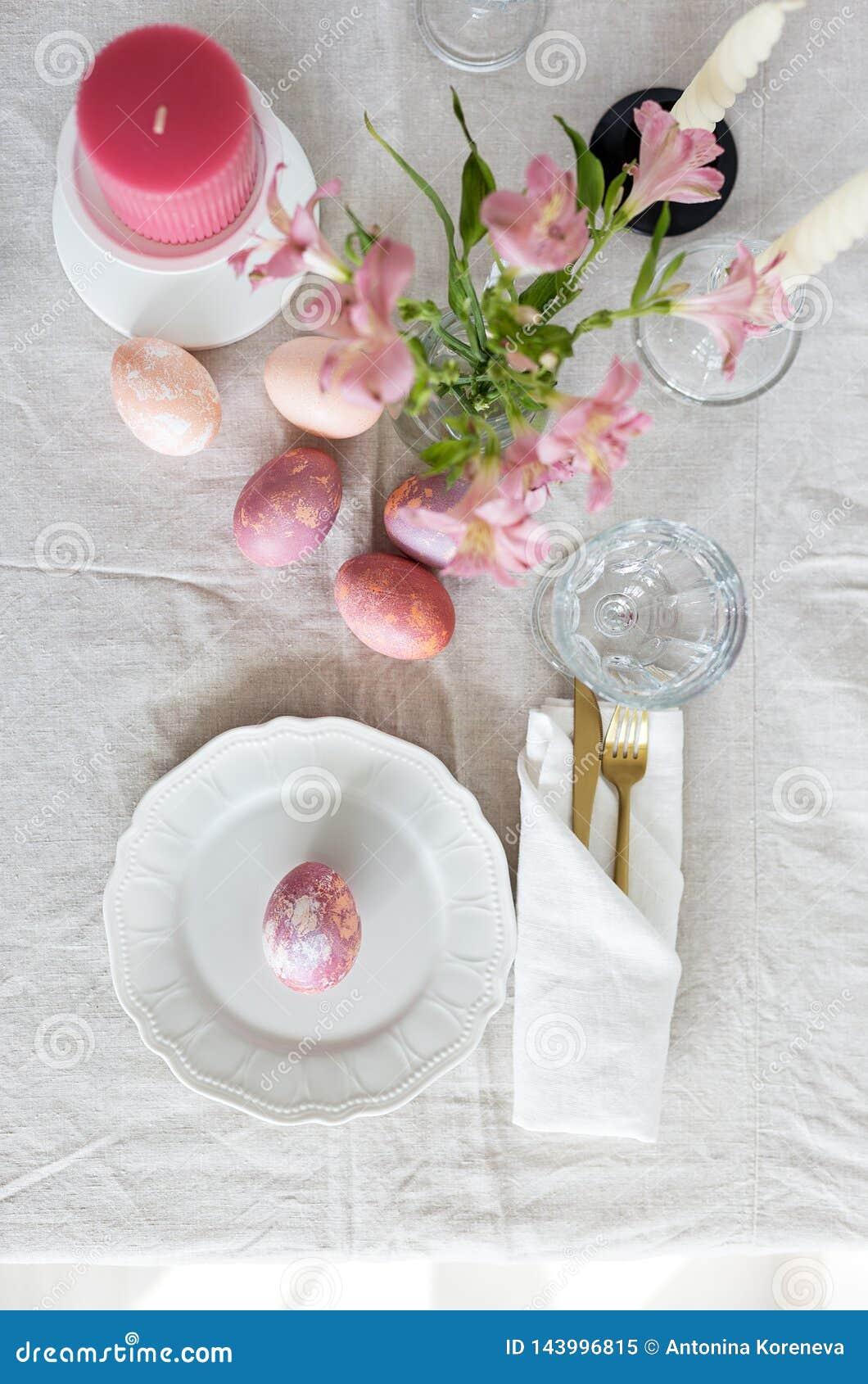 Φωτεινός εορταστικός πίνακας Πάσχας που θέτει με το τραπεζομάντιλο λινού, τα χρωματισμένα αυγά και τα λουλούδια
