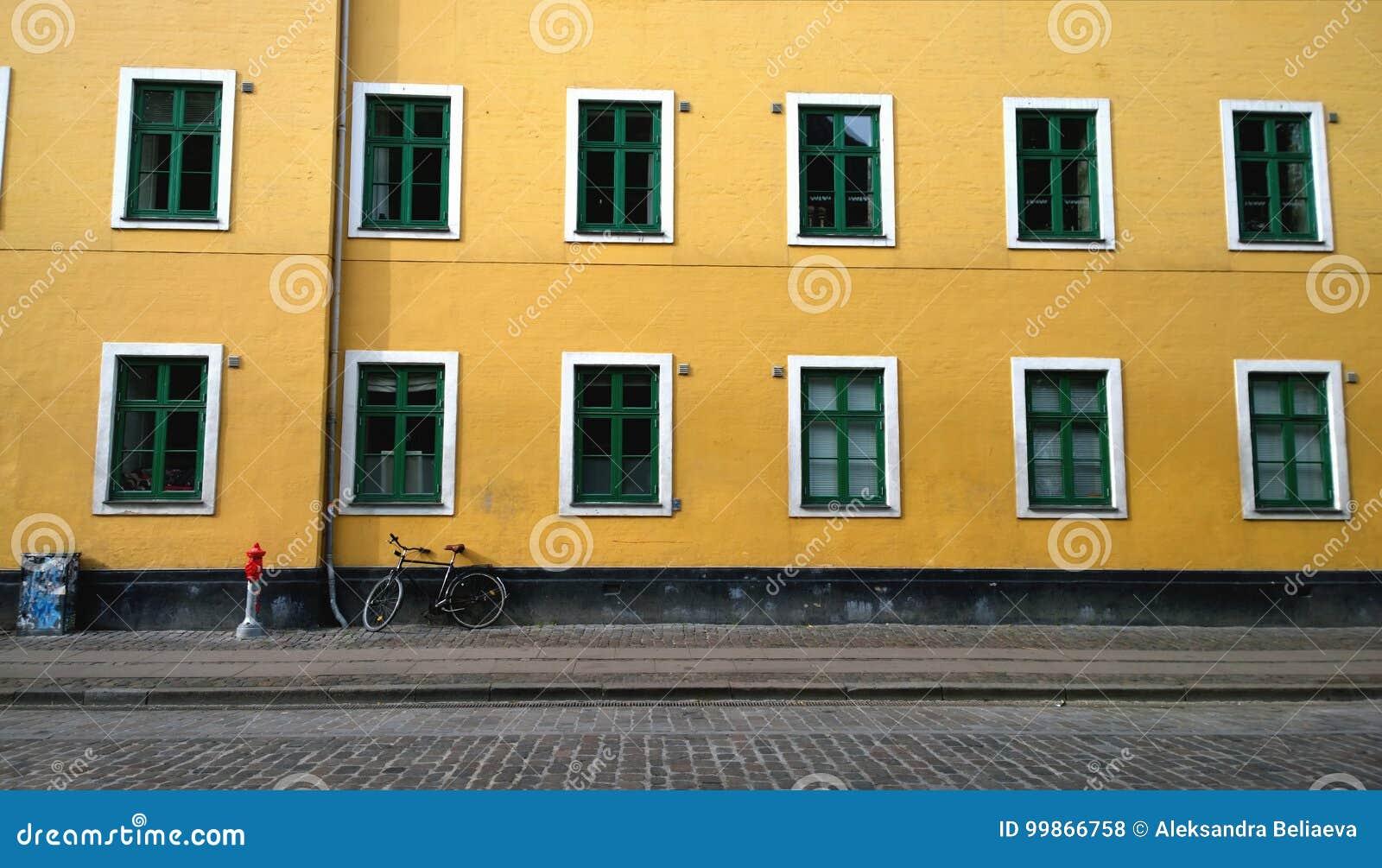 Φωτεινό κίτρινο σπίτι τοίχων με τα μέρη των όμορφων παραθύρων Στον τοίχο που κλίνει το ποδήλατο Κοντά σε μια μικρή θέση