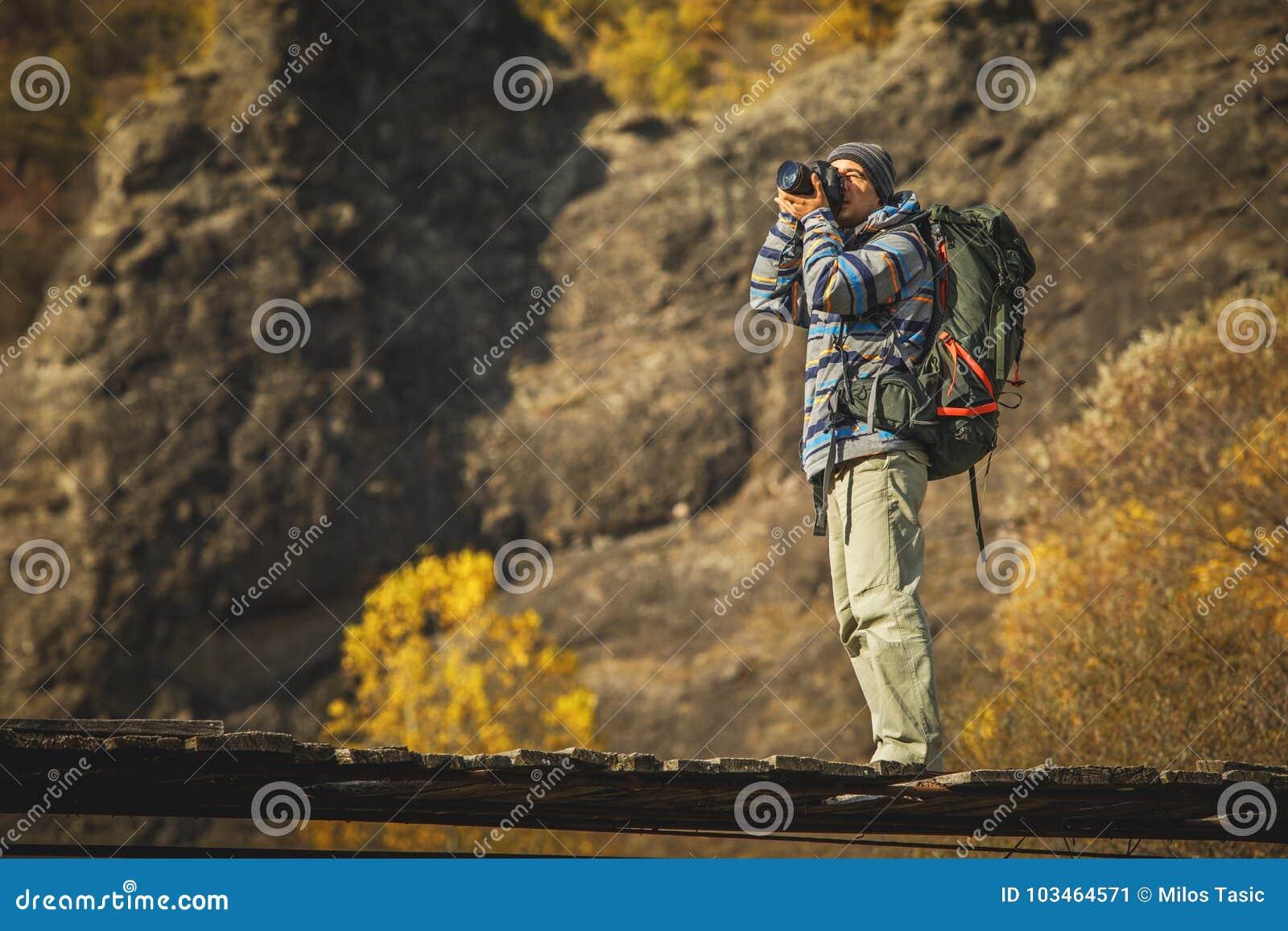 Φωτογράφος ατόμων με το μεγάλο σακίδιο πλάτης και κάμερα που παίρνει τη φωτογραφία του SU