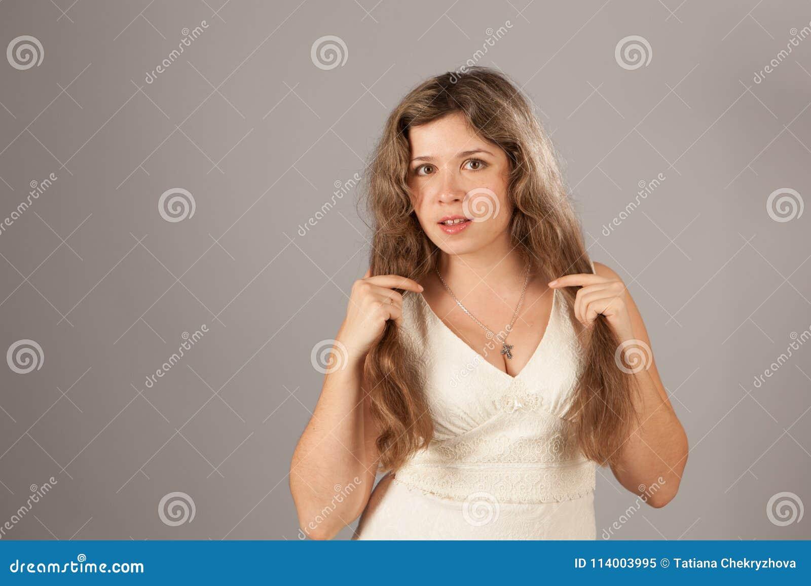 Φωτογραφία μόδας μιας νέας γυναίκας με τη σγουρή τρίχα που φορά το άσπρο φόρεμα