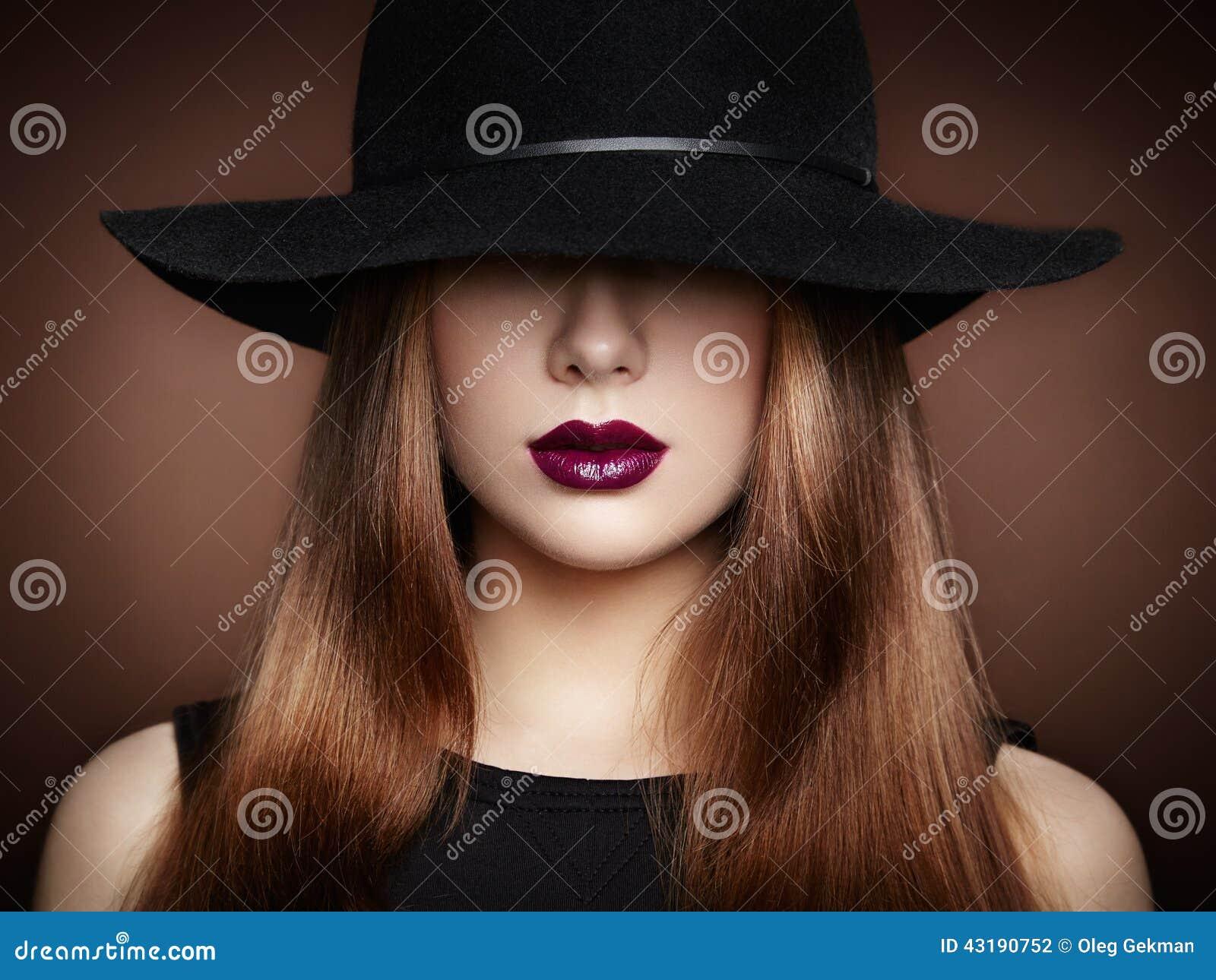 Φωτογραφία μόδας της νέας θαυμάσιας γυναίκας στο καπέλο κορίτσι ανασκόπησης που θέτει το ύδωρ