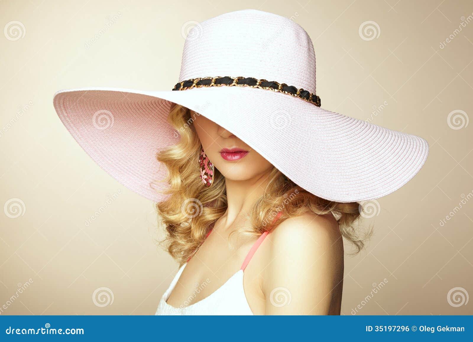 Φωτογραφία μόδας της νέας θαυμάσιας γυναίκας στο καπέλο. Τοποθέτηση κοριτσιών