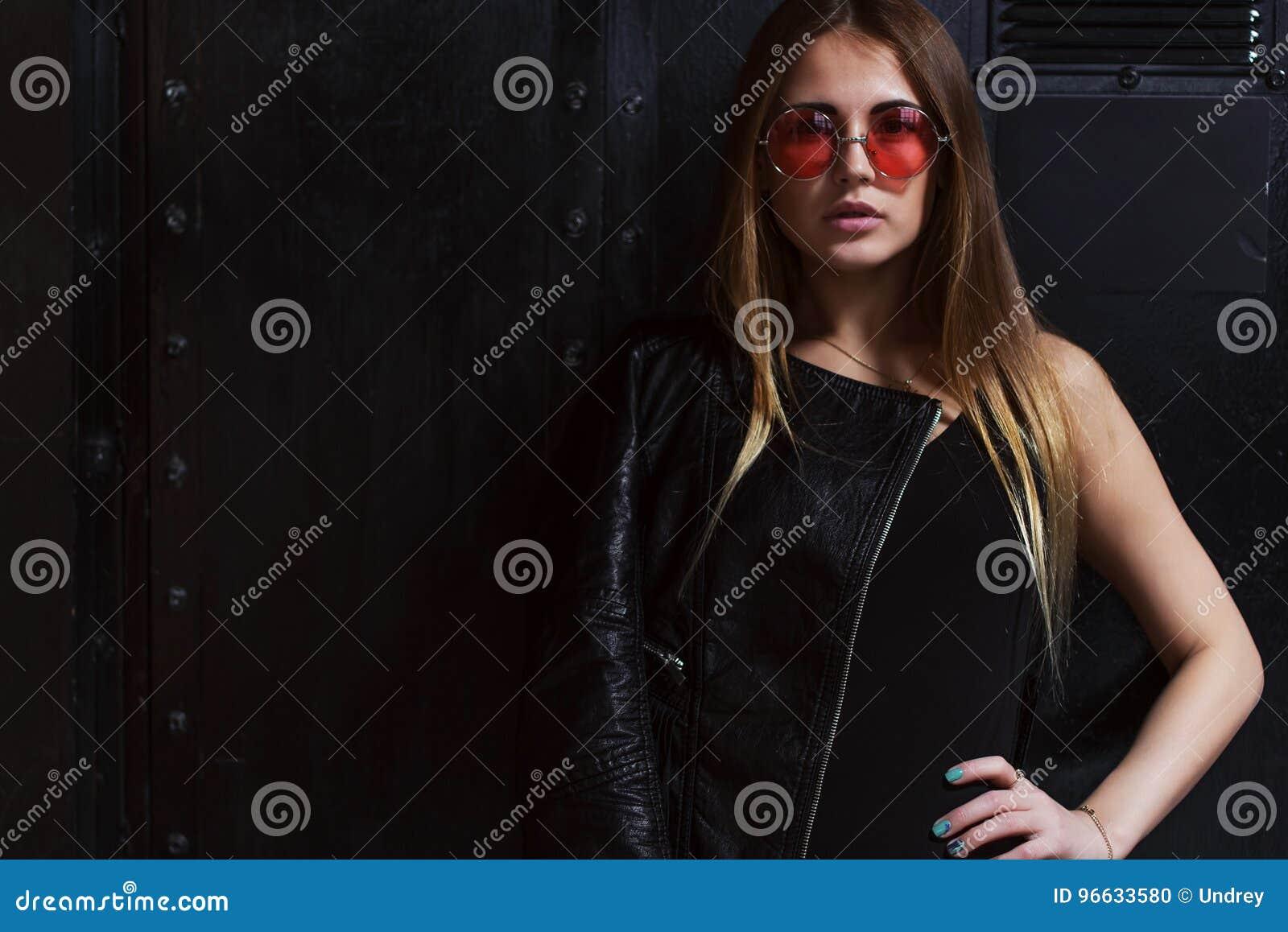 Φωτογραφία μόδας του ελκυστικού θηλυκού προτύπου στα επιθετικά ενδύματα ύφους βράχου και τα ρόδινα γυαλιά ηλίου που θέτουν στο σκ