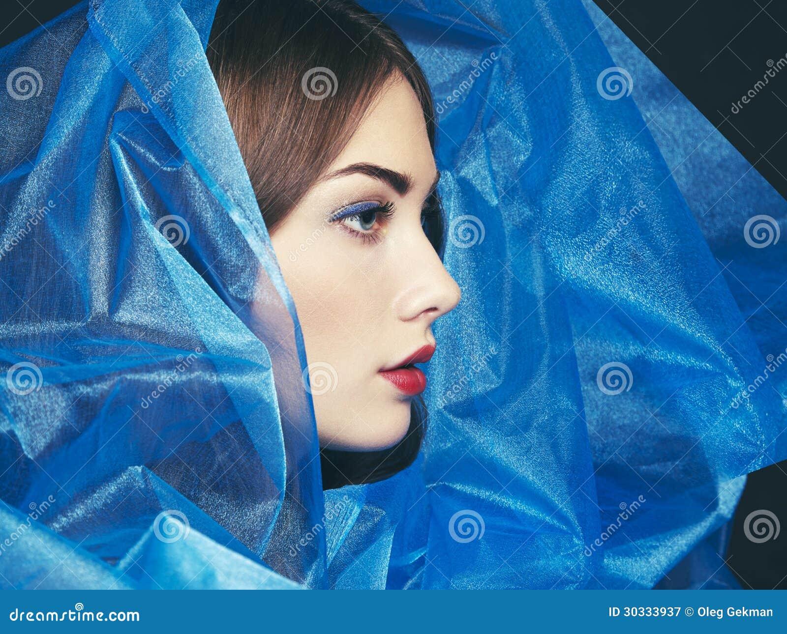 Φωτογραφία μόδας των όμορφων γυναικών κάτω από το μπλε πέπλο