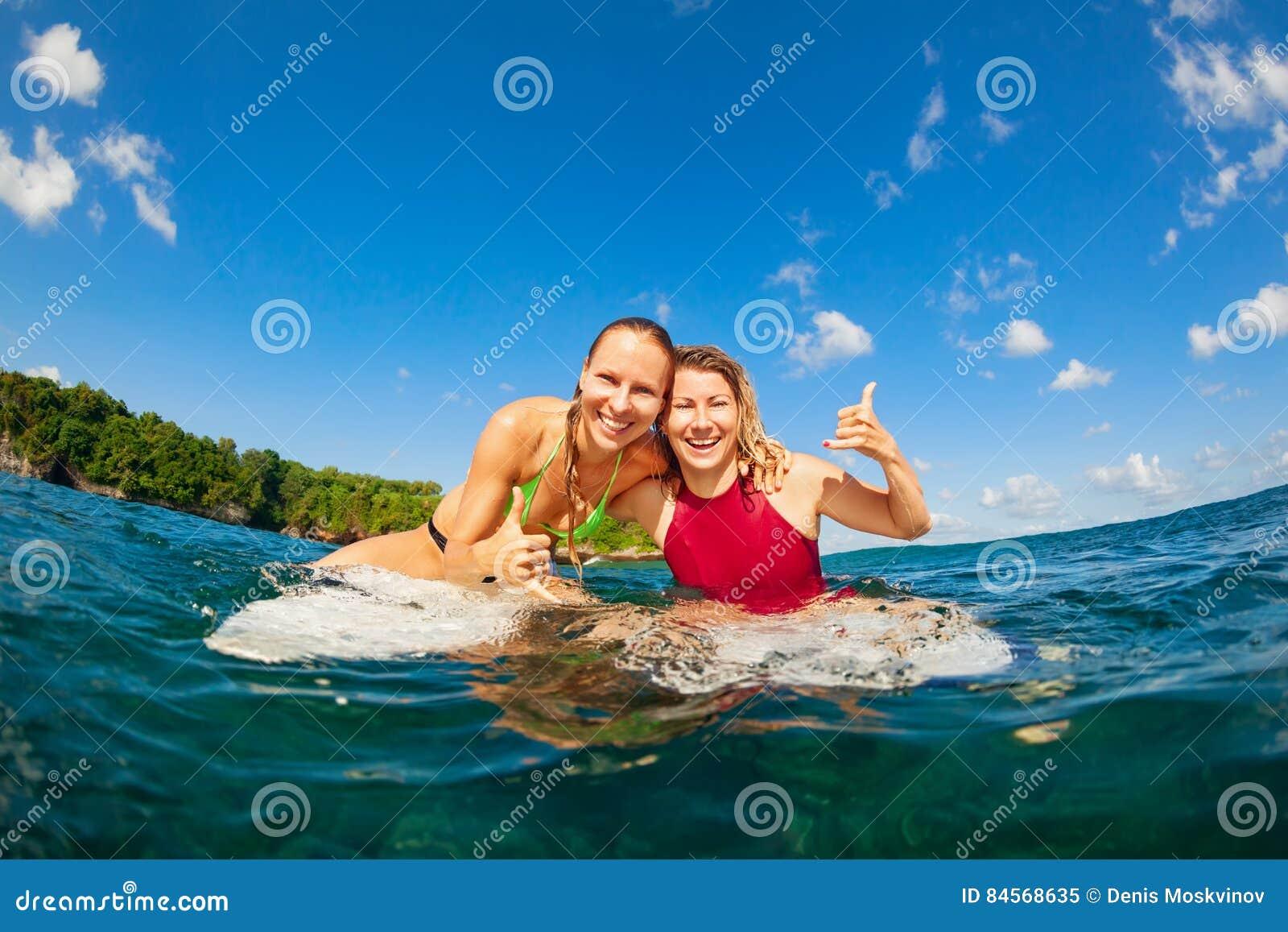 Φωτογραφία των ευτυχών κοριτσιών surfer που κάθονται στους πίνακες κυματωγών