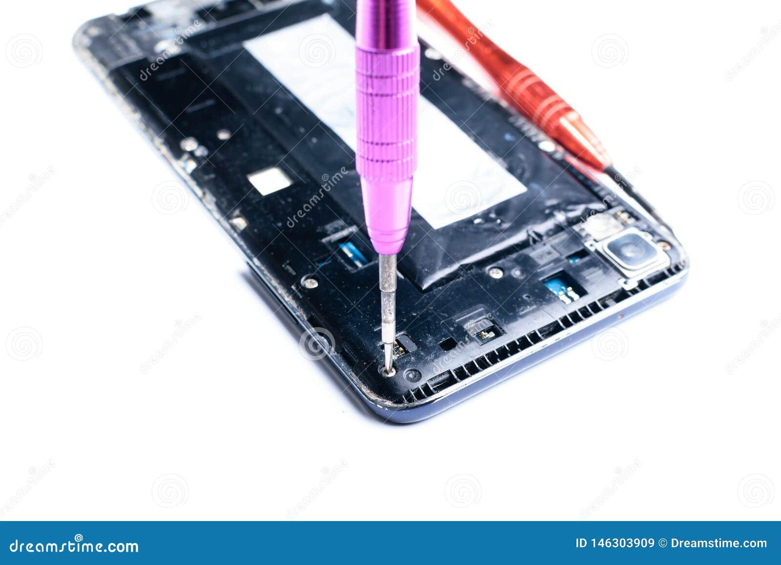 Φωτογραφίες που παρουσιάζουν τη διαδικασία ένα σπασμένο κινητό τηλέφωνο με ένα κατσαβίδι στο εργαστήριο για την επισκευή του κινη
