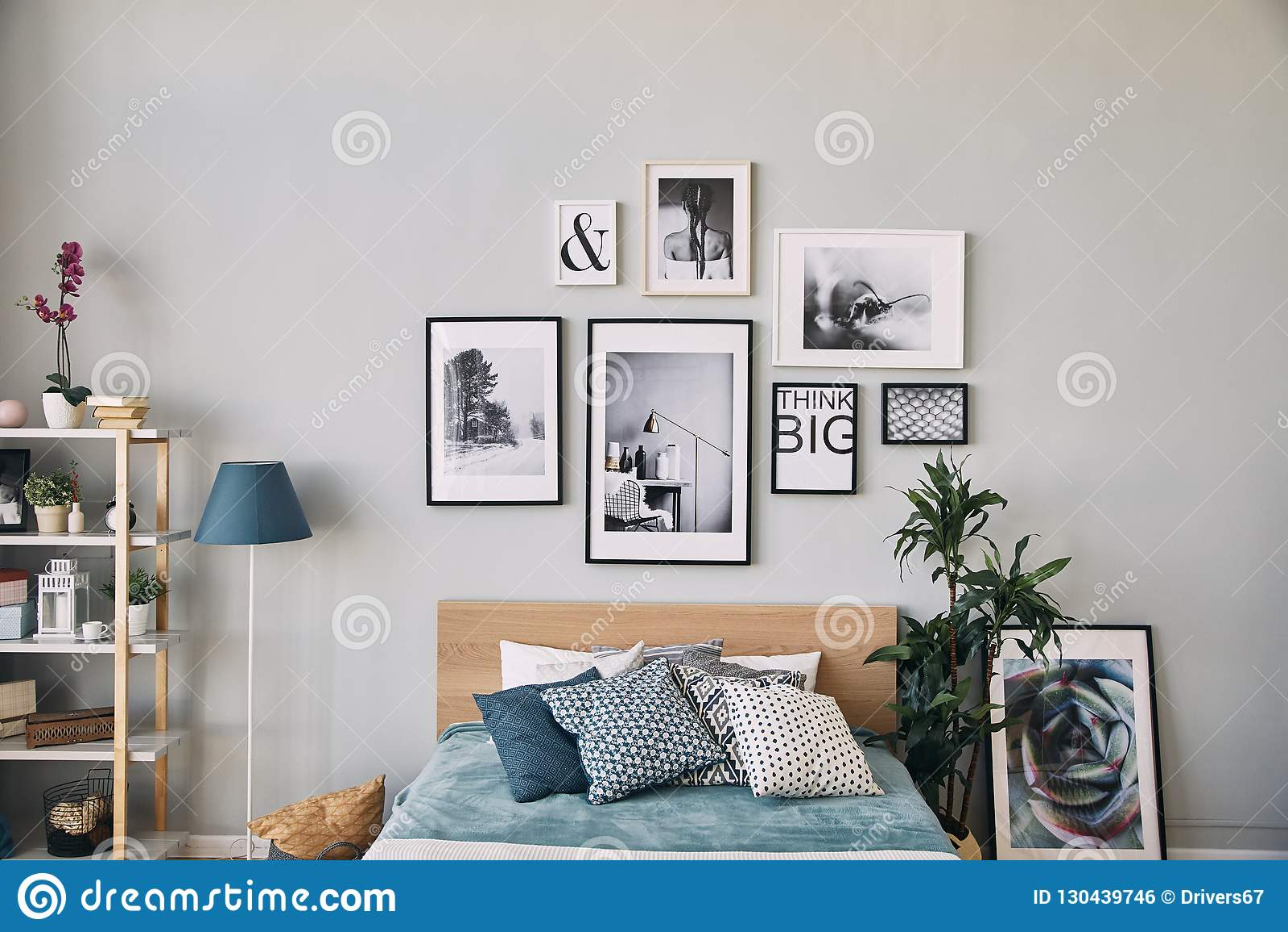 Φωτογραφίες των διαφορετικών μεγεθών σε ένα πλαίσιο που κρεμά πέρα από το κρεβάτι εσωτερικός σύγχρονος κρεβατοκάμαρων