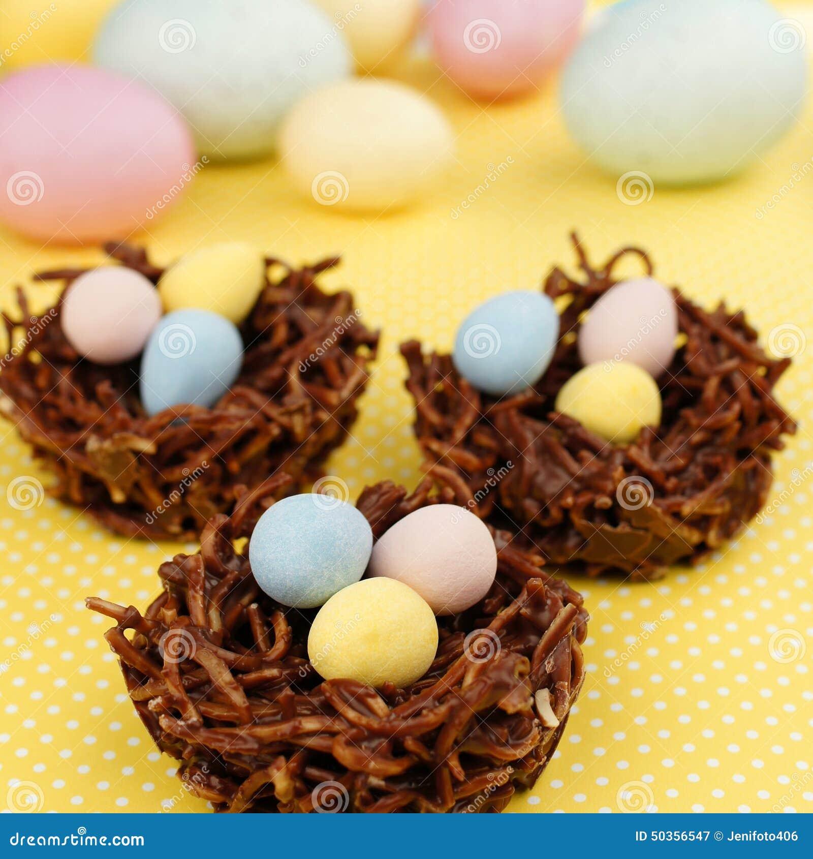 Φωλιές σοκολάτας άνοιξης που γεμίζουν με τα αυγά Πάσχας σε κίτρινο