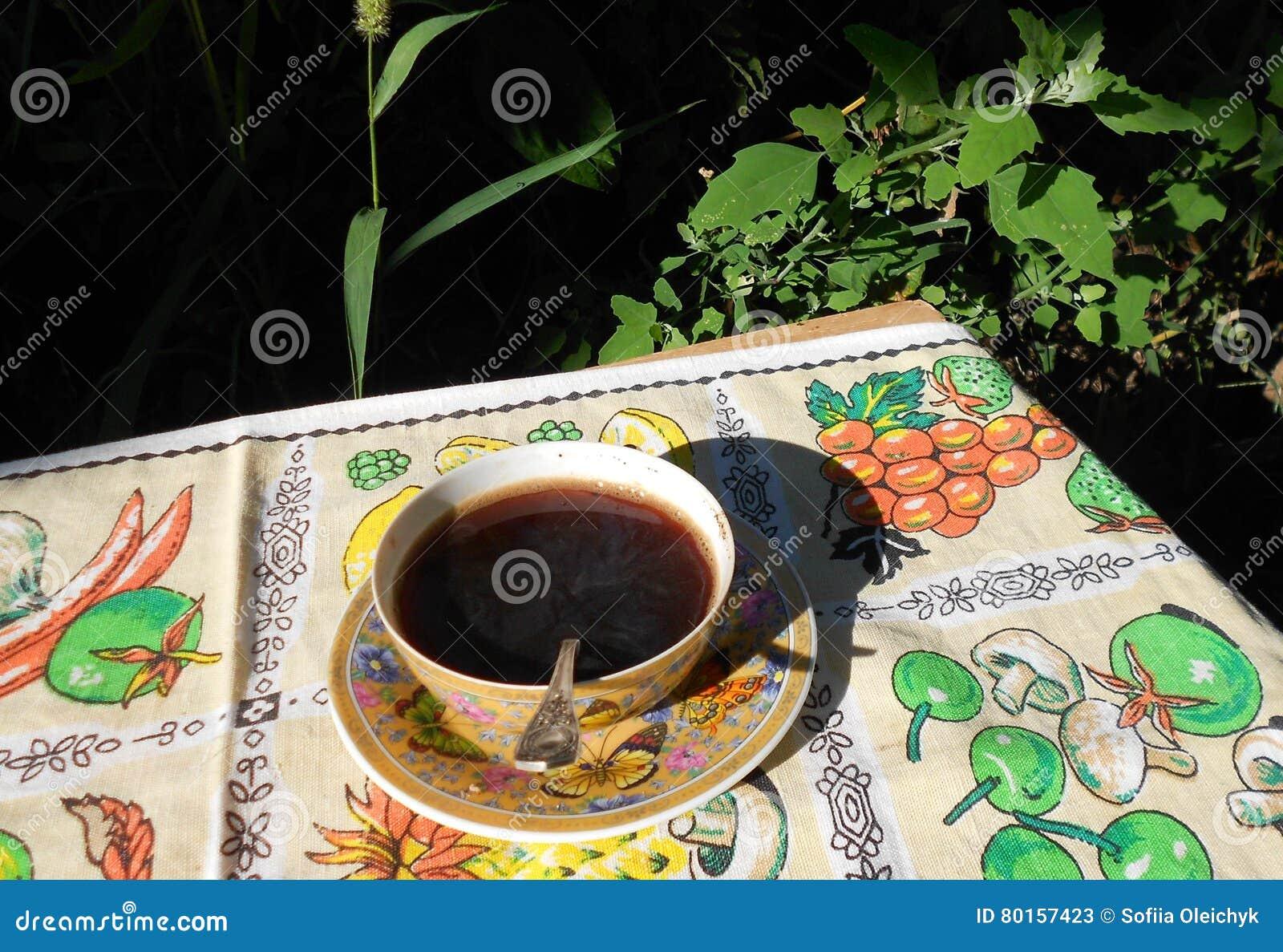 Φλιτζάνι του καφέ σε ένα υπόβαθρο της βλάστησης