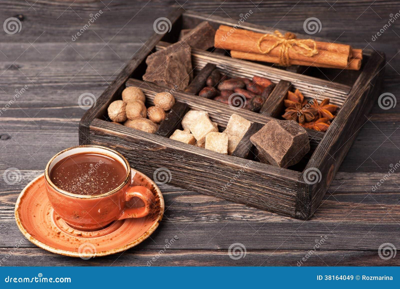 Φλυτζάνι της καυτής σοκολάτας και του εκλεκτής ποιότητας ξύλινου κιβωτίου με τα καρυκεύματα και τη σκοτεινή σοκολάτα