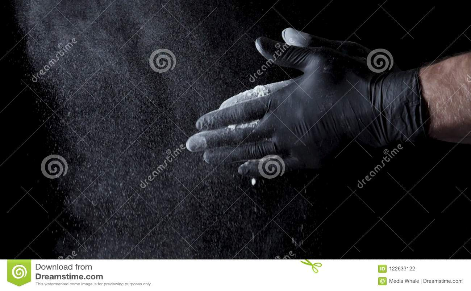 Χέρια βαμβακιού με το αλεύρι στο μαύρο υπόβαθρο Πλαίσιο Αρχιμάγειρας που χτυπά τα χέρια που καλύπτονται στο αλεύρι