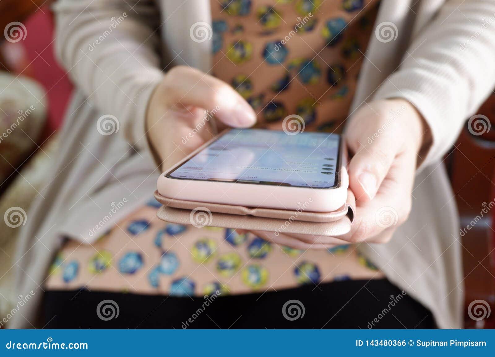 Χέρια γυναικών που κρατούν το κινητό τηλέφωνο, επικοινωνία μηνύματος