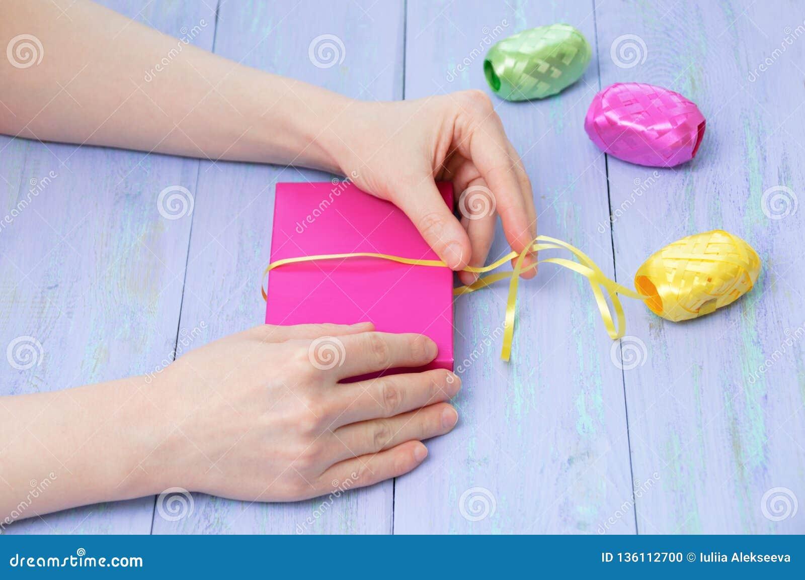 Χέρια γυναικών που τυλίγονται σε ένα ρόδινο κιβώτιο δώρων με ένα κίτρινο ιώδες ξύλινο υπόβαθρο κορδελλών Cose-επάνω