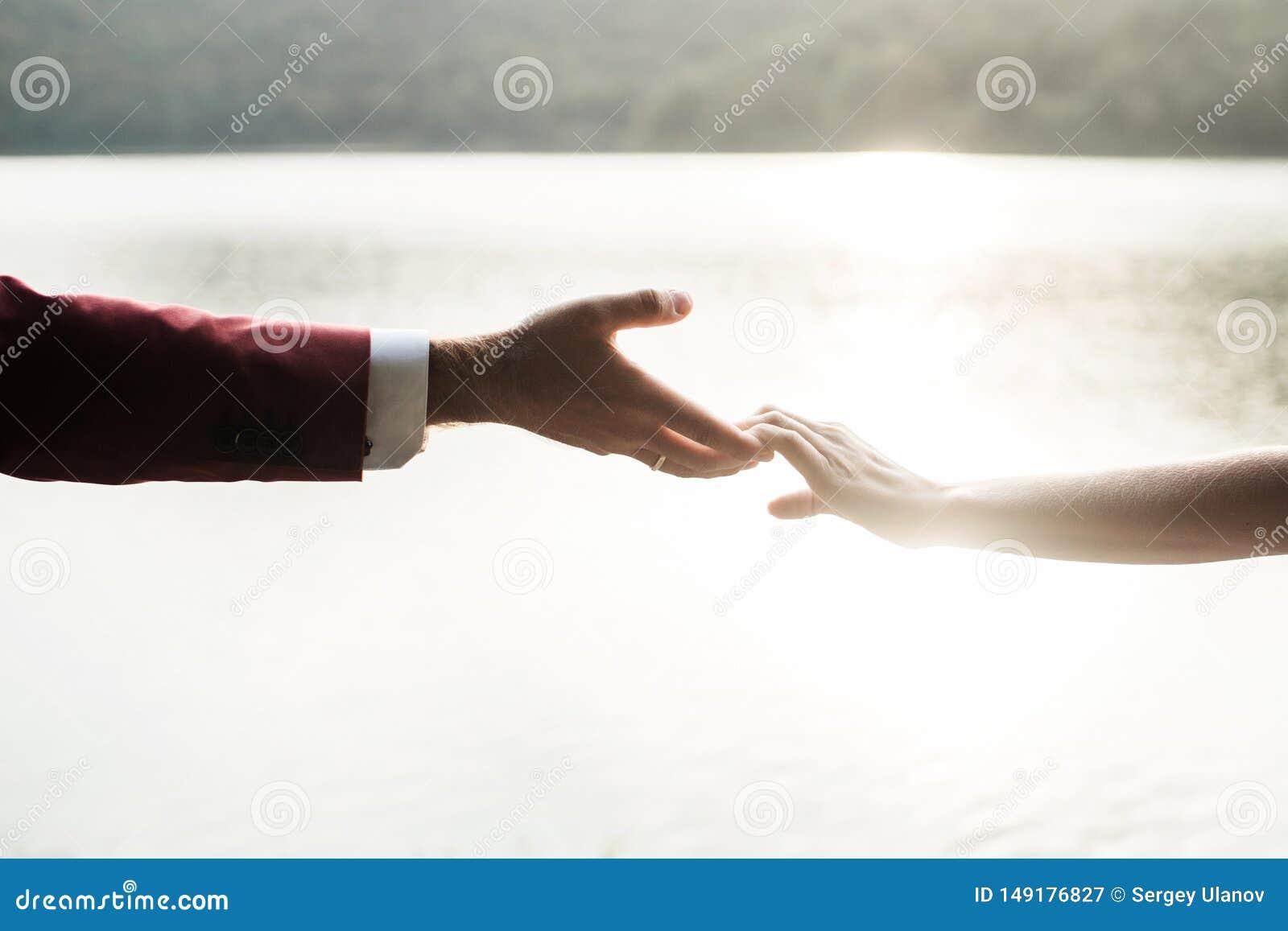 Χέρια εκμετάλλευσης ανδρών και γυναικών στο ηλιοβασίλεμα