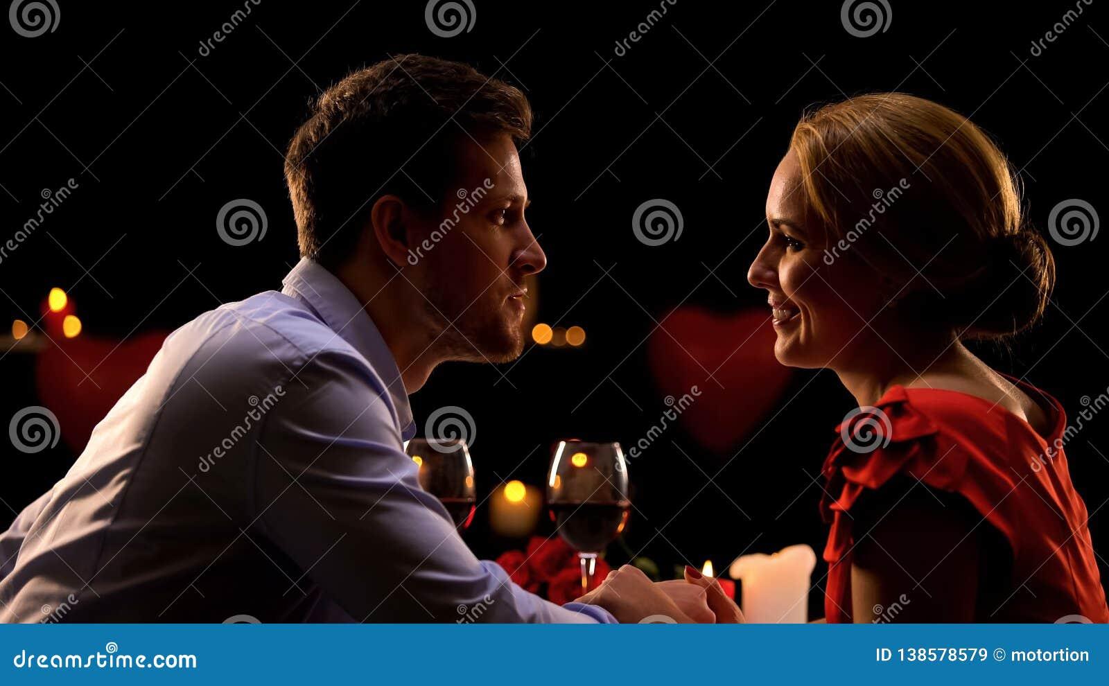 Χέρια εκμετάλλευσης ζεύγους και θαυμασμός του ενός τον άλλον κατά τη ρομαντική ημερομηνία στο εστιατόριο
