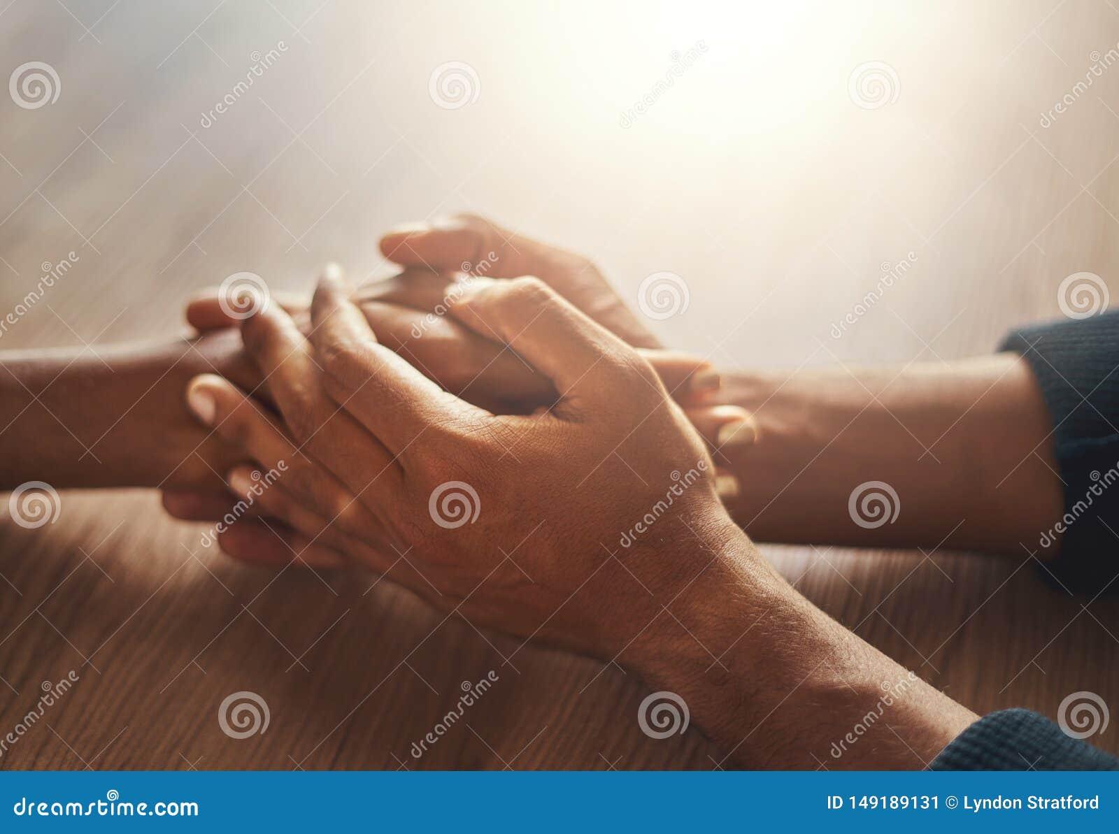 Χέρια εκμετάλλευσης χεριών ζεύγους στο ξύλινο γραφείο