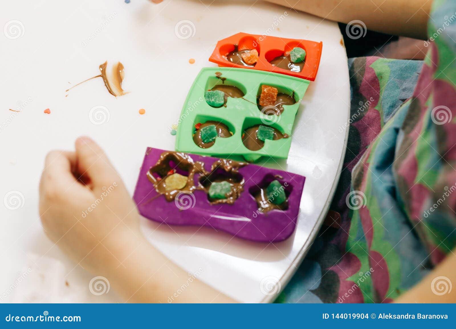 Χέρια ενός παιδιού, μια κύρια κατηγορία στο μαγείρεμα της σοκολάτας, δίπλωμα των φρούτων και της σοκολάτας στις φόρμες
