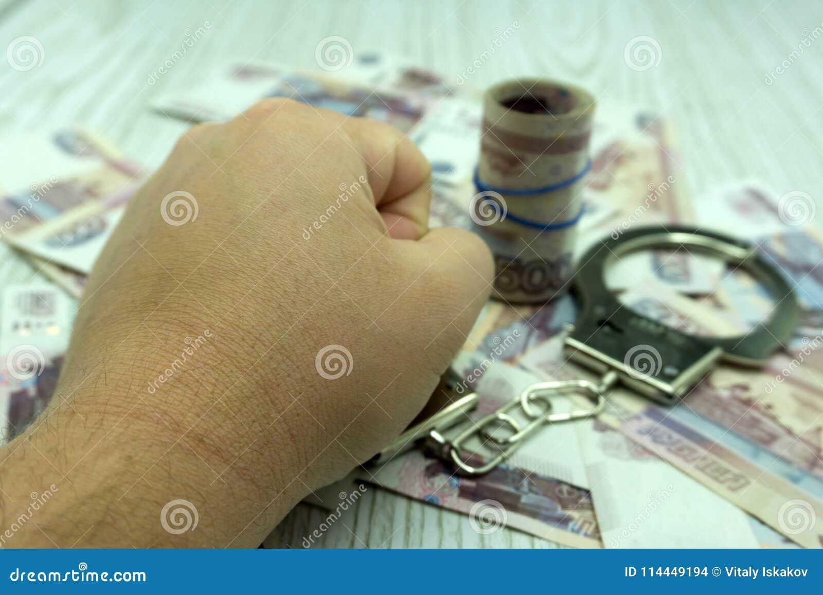 Χέρια με τα δολάρια στην αλυσίδα σε ένα μαύρο υπόβαθρο