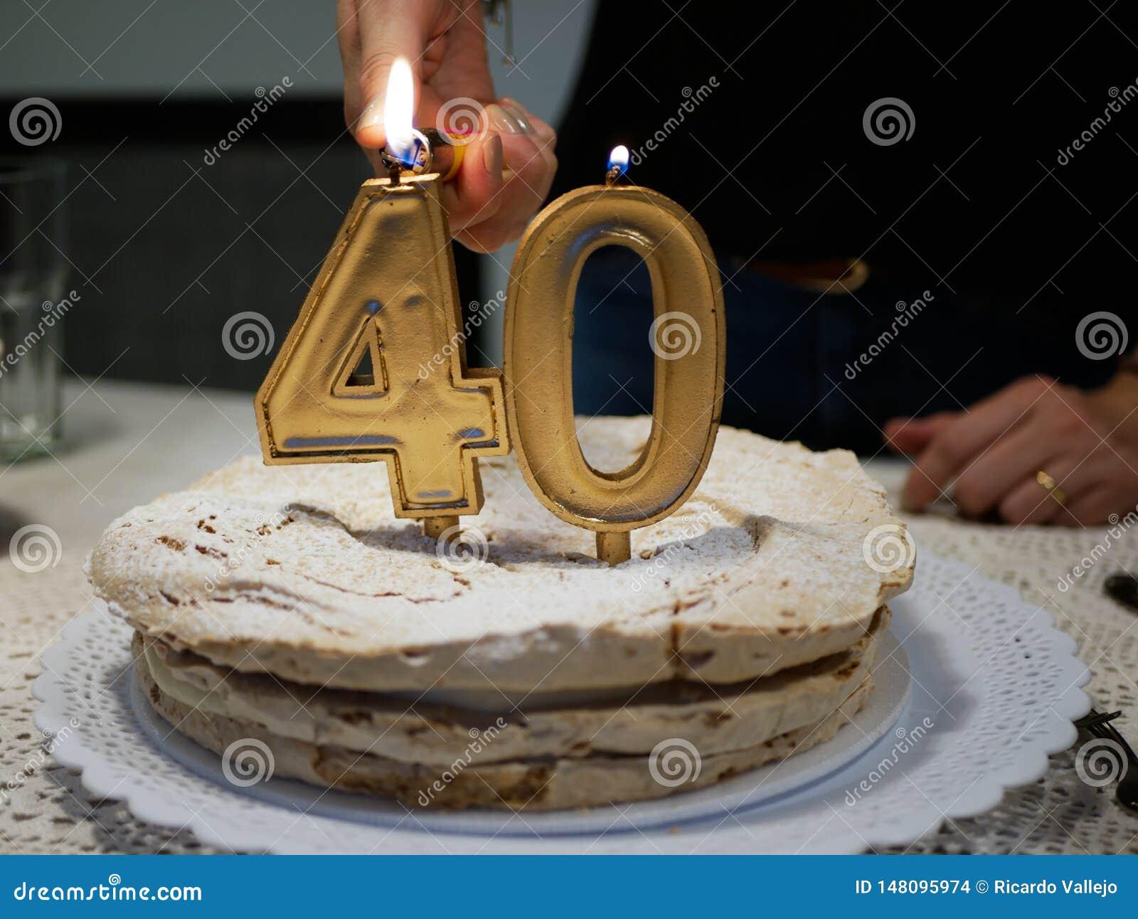 Χέρια μιας γυναίκας που ανάβει τα χρυσά κεριά τέσσερα και μηδέν ενός εορτασμού κέικ γενεθλίων 40ου