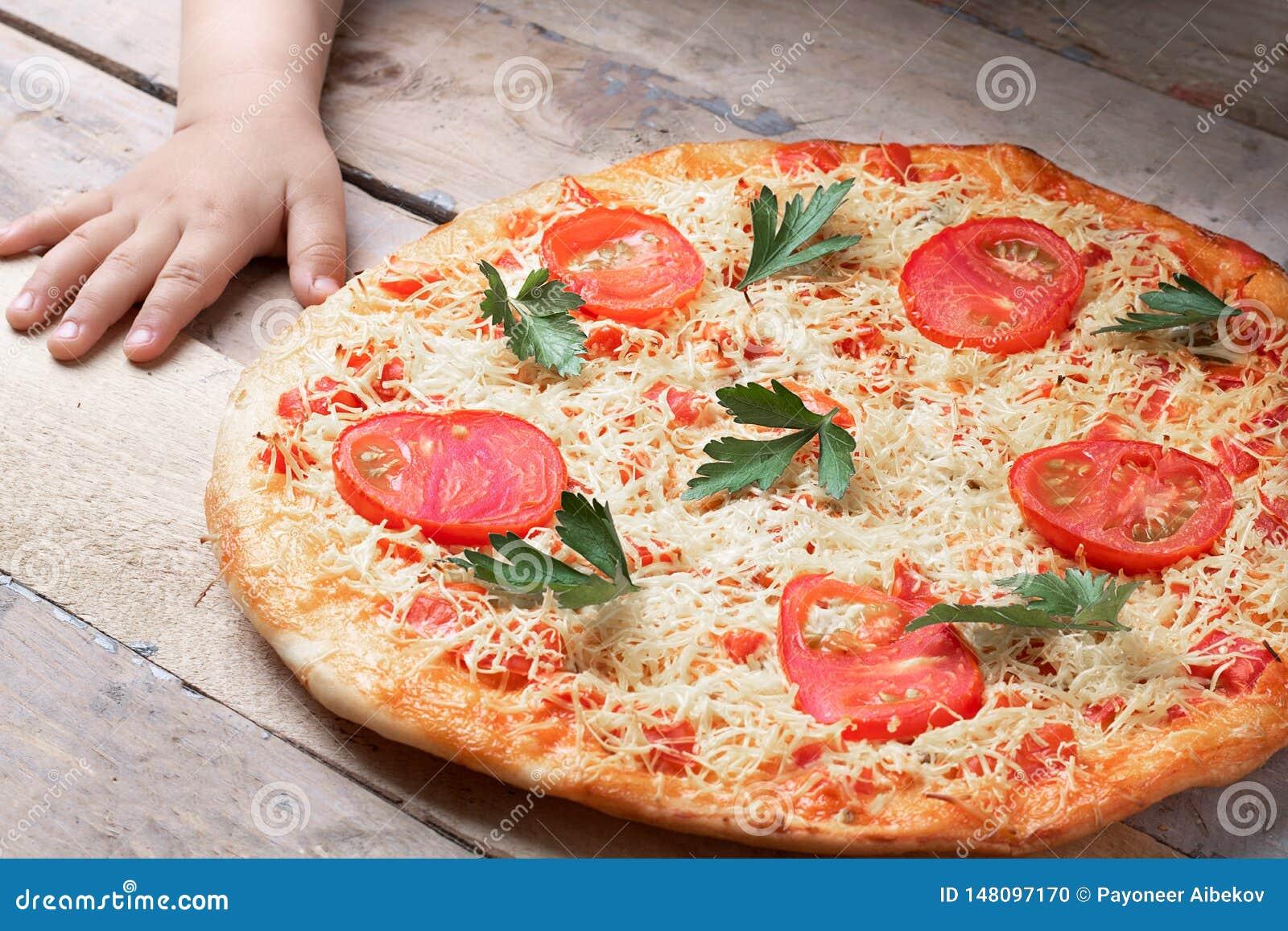 Χέρια παιδιών με τη Μαργαρίτα Pizza με την ντομάτα και το κόκκινο τσίλι δύο στον γκρίζο πίνακα, τη τοπ άποψη και τη θέση για το κ