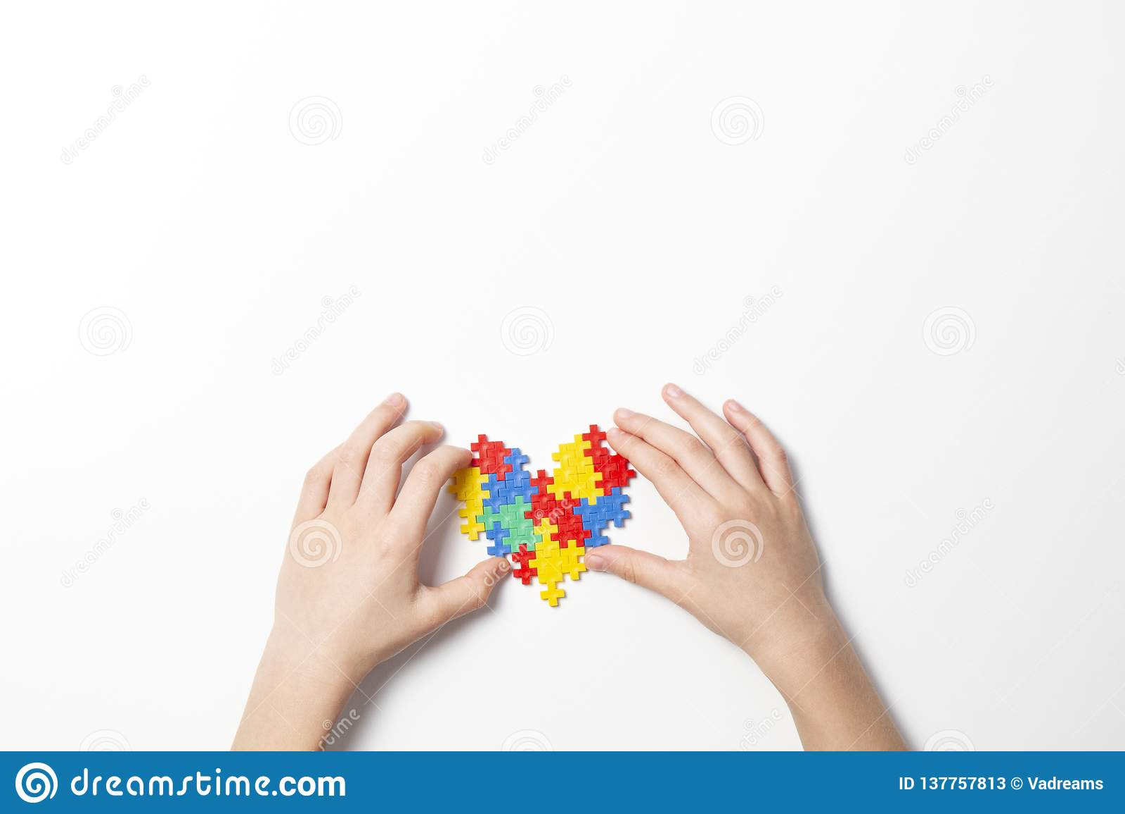 Χέρια παιδιών που κρατούν τη ζωηρόχρωμη καρδιά στο άσπρο υπόβαθρο Έννοια ημέρας συνειδητοποίησης παγκόσμιου αυτισμού