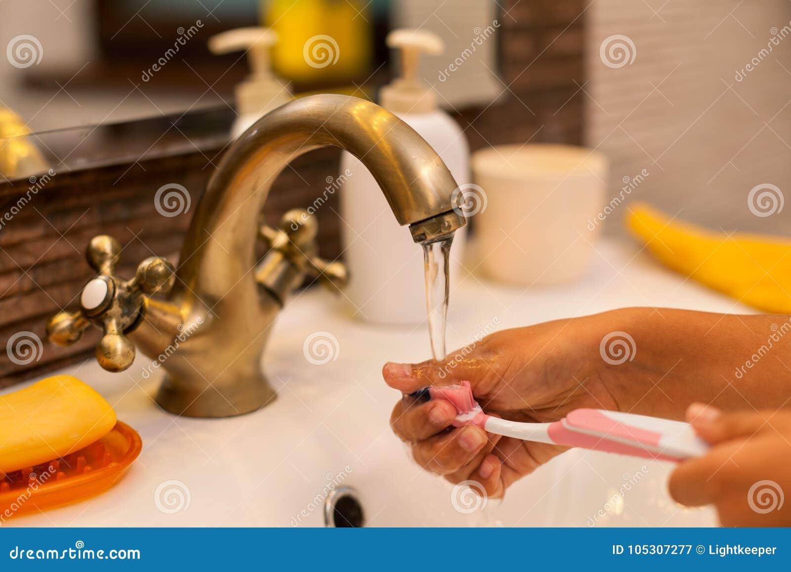 Χέρια παιδιών που πλένουν και που ξεπλένουν μια οδοντόβουρτσα