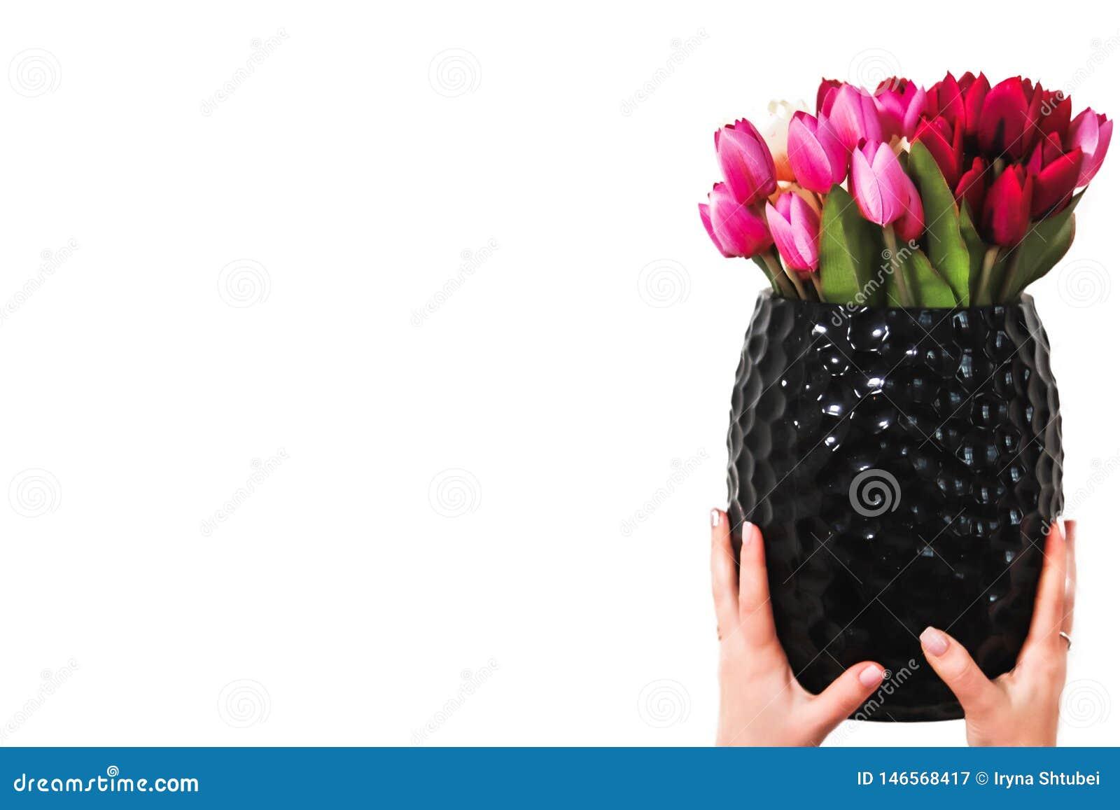 Χέρια που κρατούν μια ανθοδέσμη των λουλουδιών σε ένα βάζο