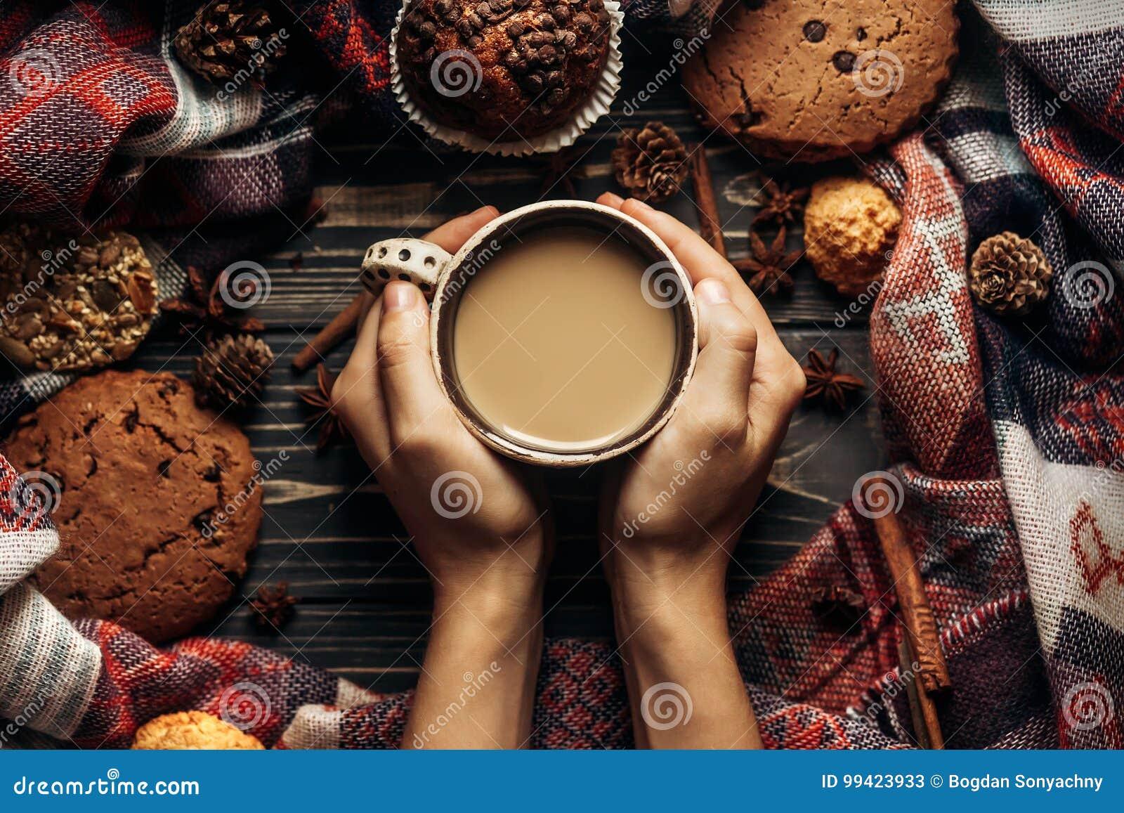 Χέρια που κρατούν τα μπισκότα και τα καρυκεύματα καφέ στο ξύλινο αγροτικό backgro