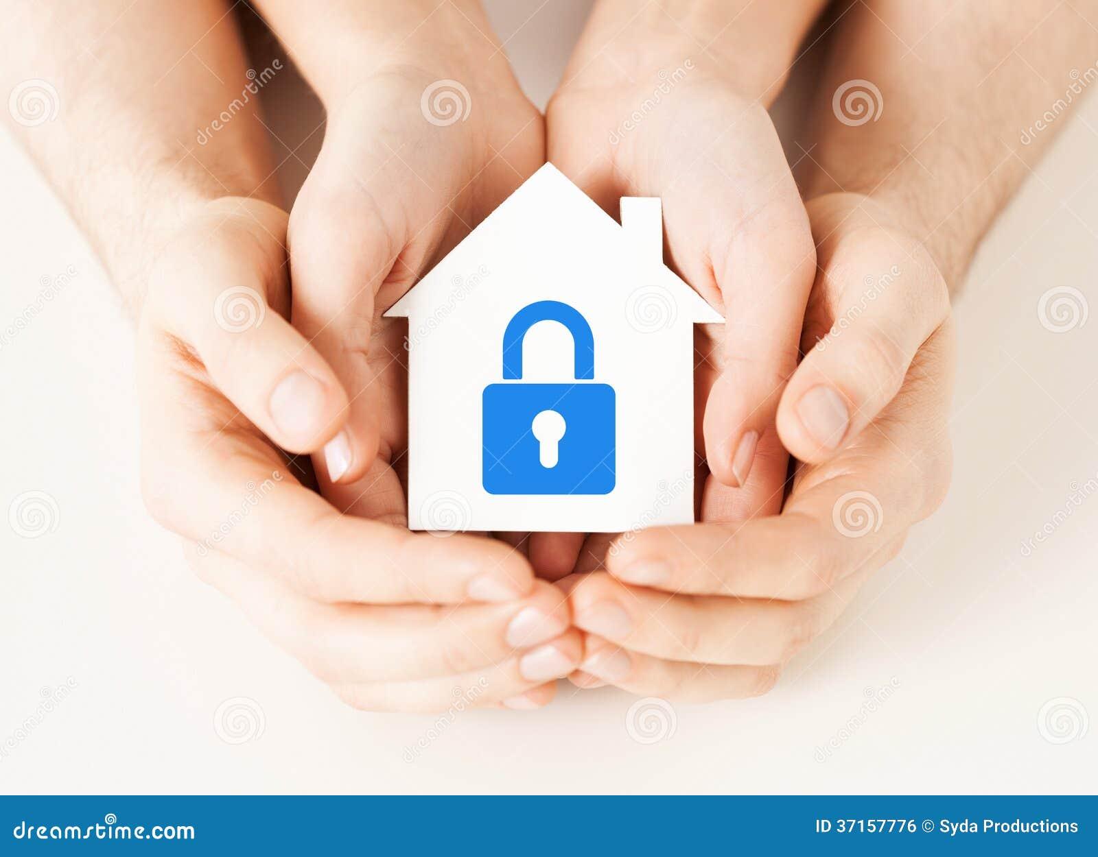 Χέρια που κρατούν το σπίτι εγγράφου με την κλειδαριά