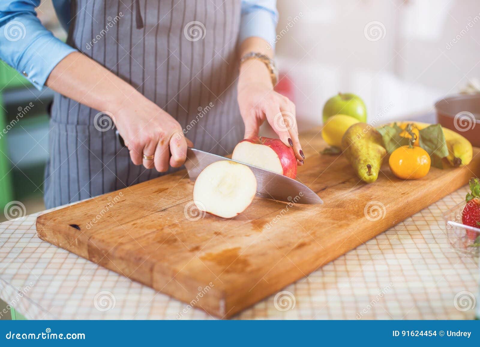 Χέρια που κόβουν ένα μήλο στον τεμαχίζοντας πίνακα Νέα γυναίκα που προετοιμάζει μια σαλάτα φρούτων στην κουζίνα της