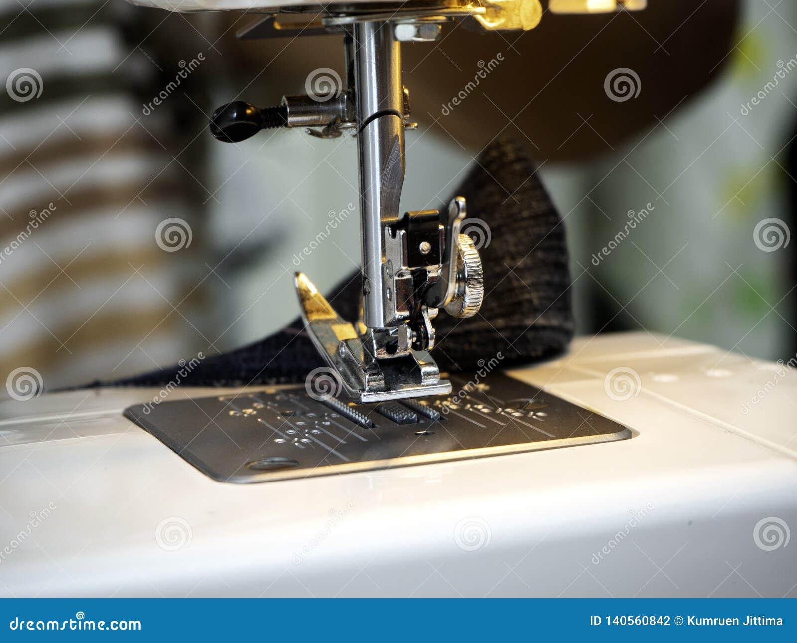Χέρια που λειτουργούν στη ράβοντας μηχανή