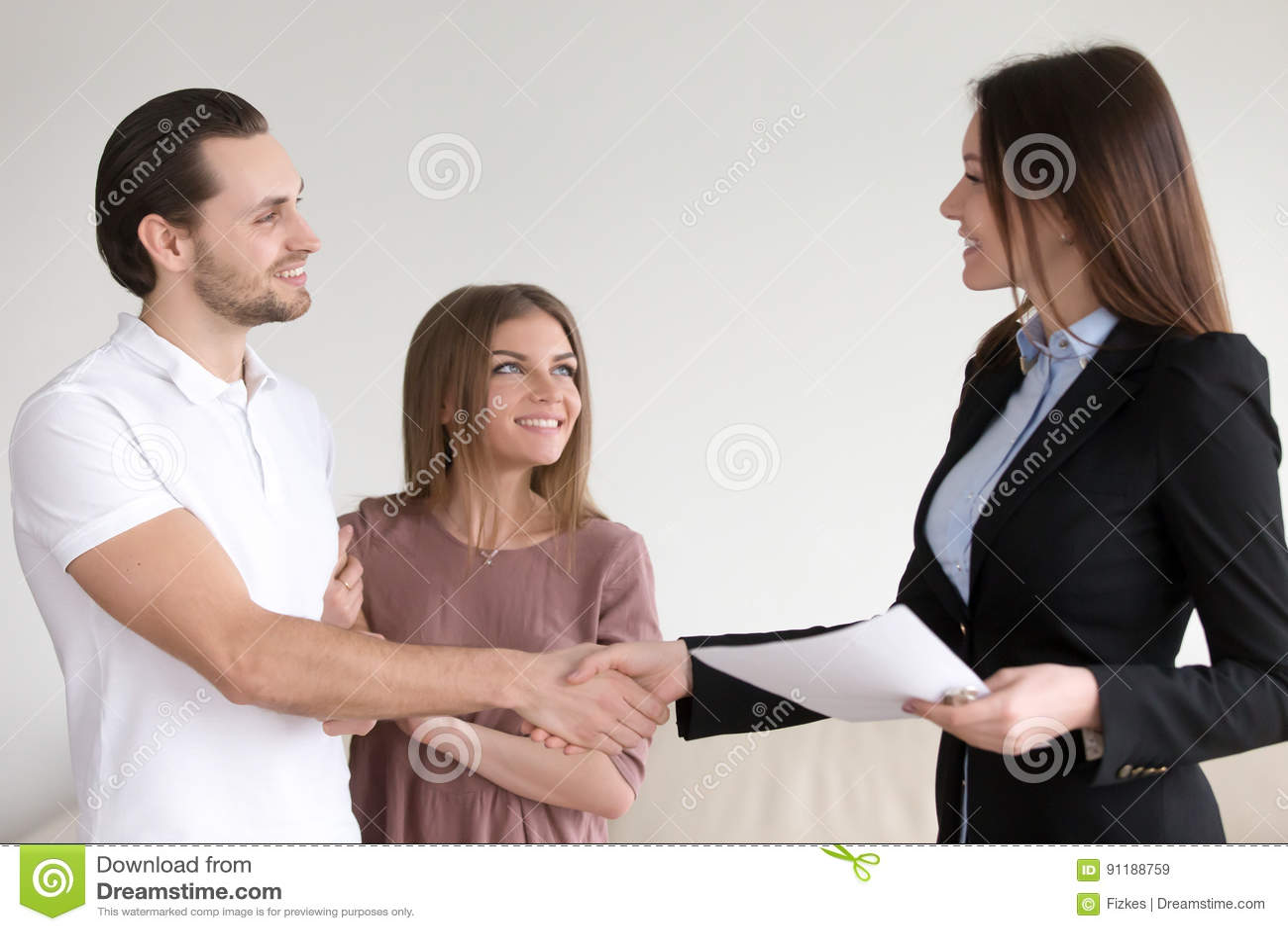 78fb7d67f4a Χέρια τινάγματος παντρεμένου ζευγαριού με το κτηματομεσίτη στο νέο ...