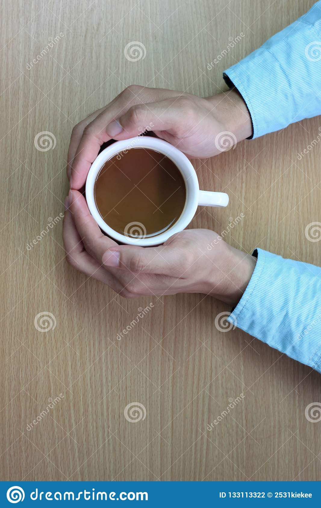χέρια του ατόμου για να αγκαλιάσει το άσπρο φλυτζάνι καφέ στον καφετή πίνακα και
