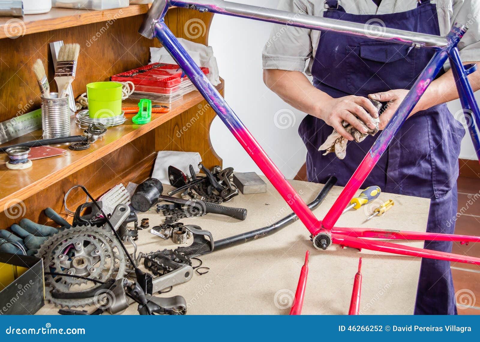 Χέρια του πραγματικού ποδηλάτου πλαισίων ποδηλάτων μηχανικού καθαρίζοντας