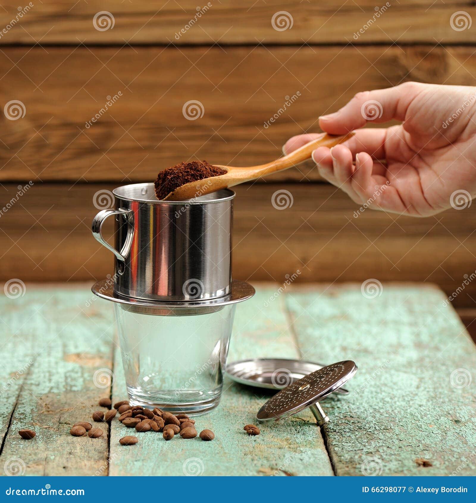 Χέρι γυναίκας που βάζει τον επίγειο καφέ στο γαλλικό φίλτρο μετάλλων σταλαγματιάς