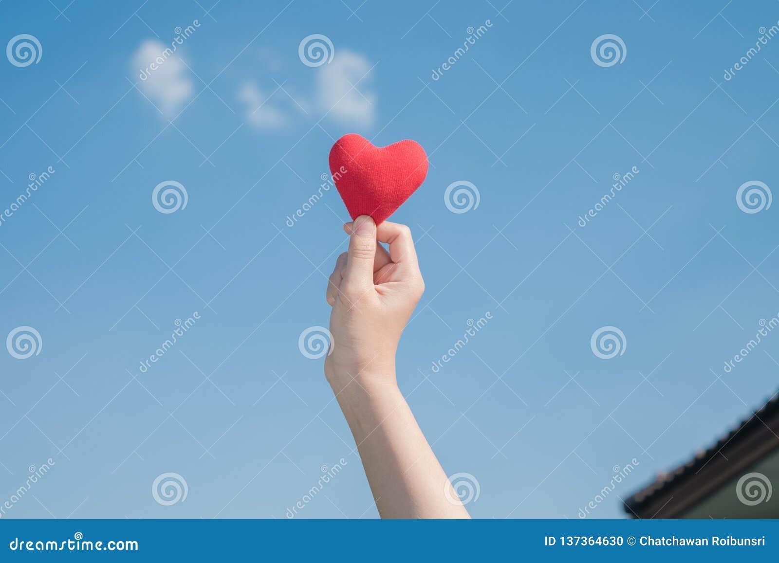 Χέρι γυναικών που κρατά μια κόκκινη καρδιά με ένα φωτεινό μπλε υπόβαθρο άνδρας αγάπης φιλιών έννοιας στη γυναίκα