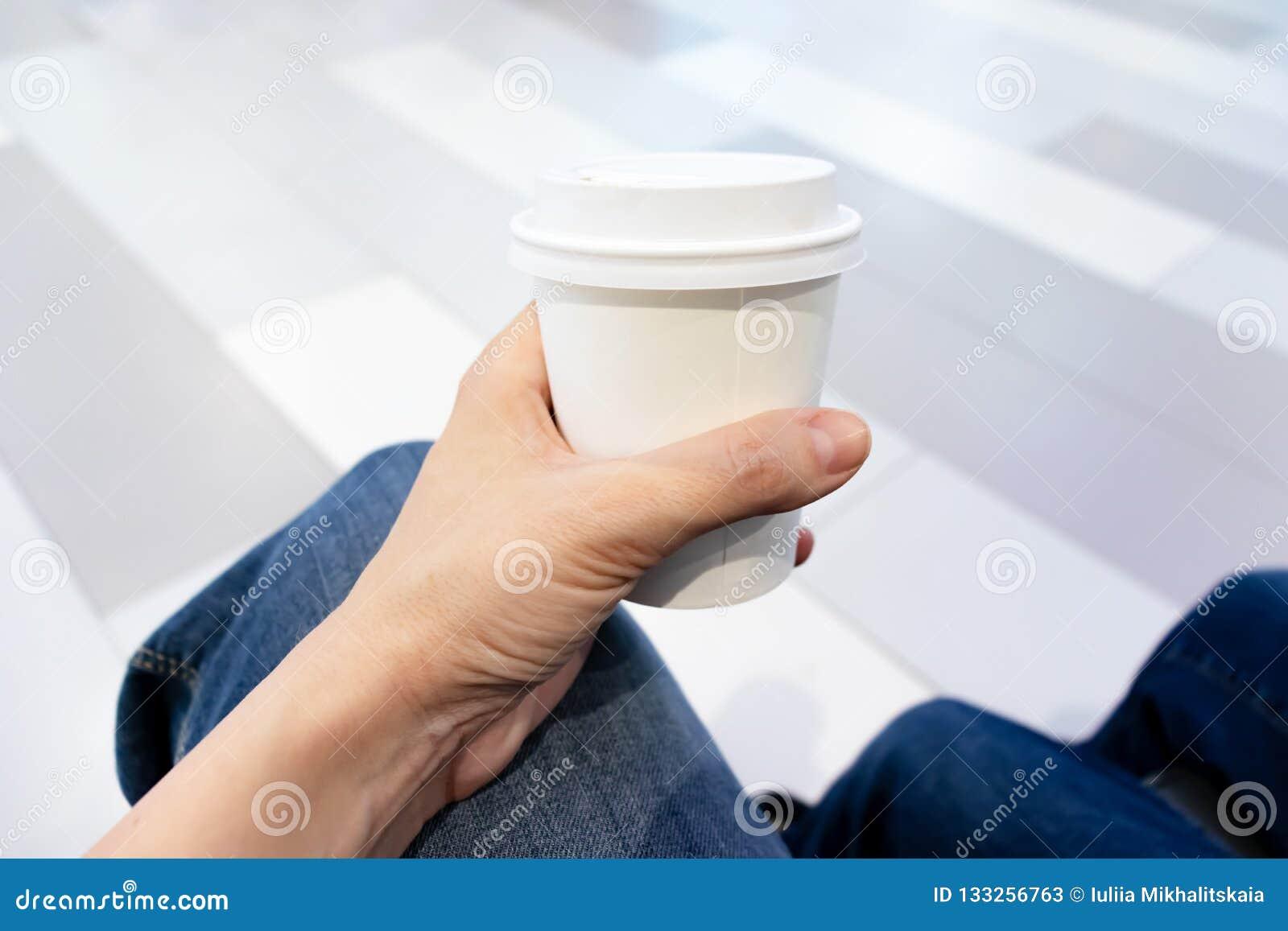 Χέρι γυναικών που κρατά το άσπρο φλιτζάνι του καφέ εγγράφου disposadle