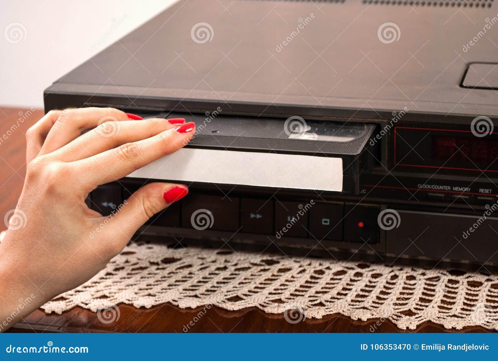 Χέρι γυναικών που παρεμβάλλει την κενή κασέτα VHS στο παλαιό βίντεο εγγραφής