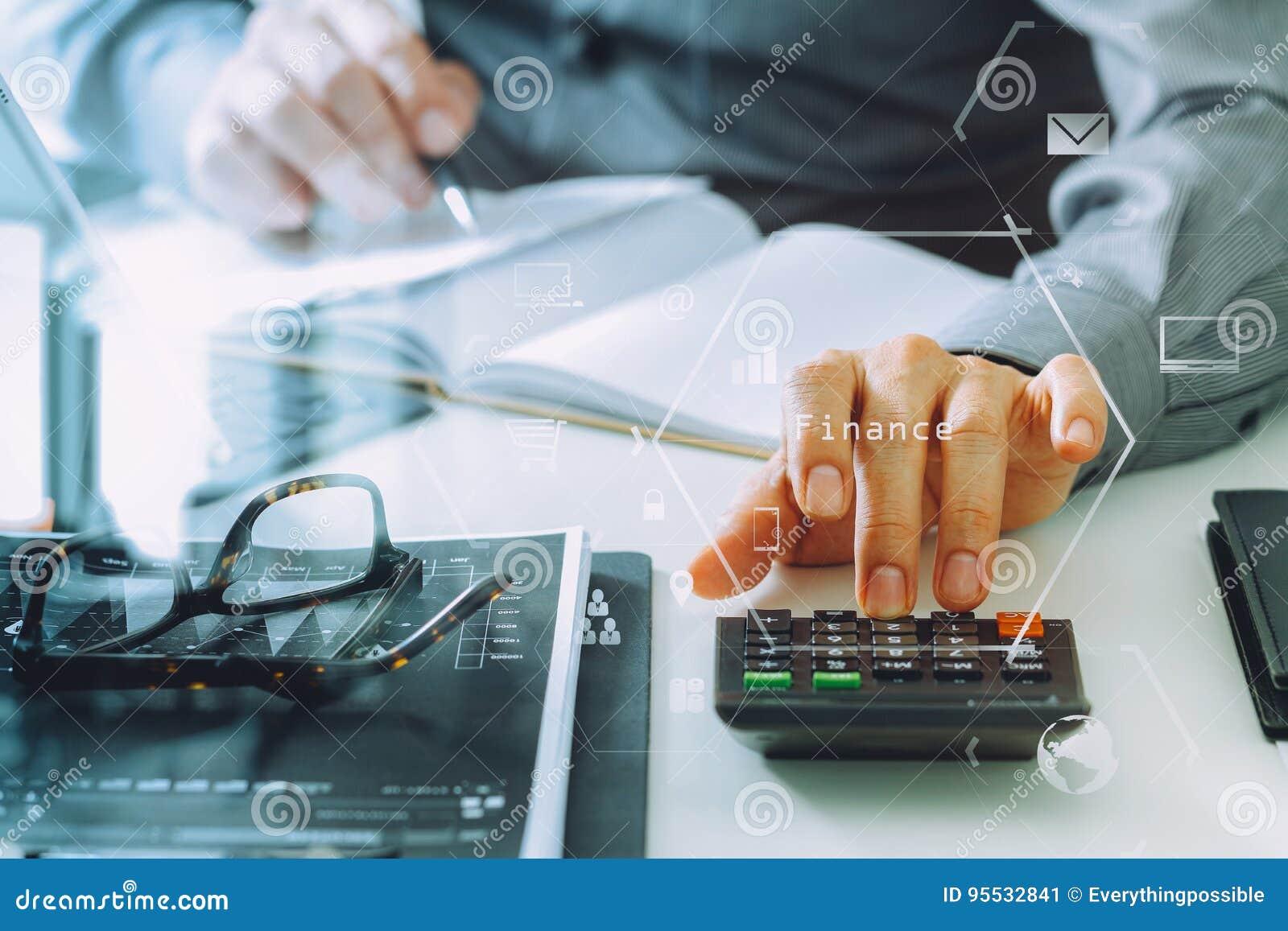 χέρι επιχειρηματιών που λειτουργεί με τους πόρους χρηματοδότησης για το κόστος και τον υπολογιστή