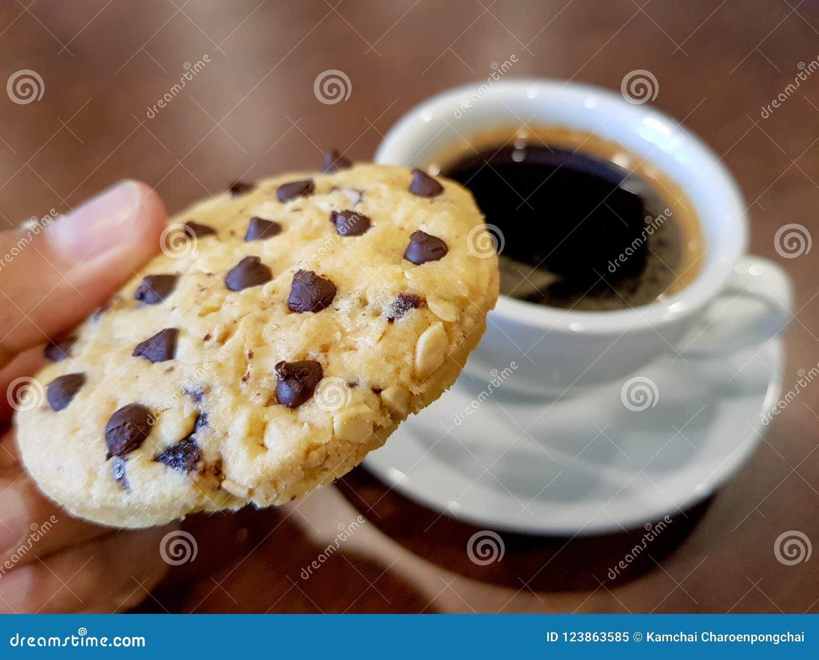 Χέρι μπισκότων τσιπ σοκολάτας pickd στο στόμα με ένα φλυτζάνι του μαύρου καφέ