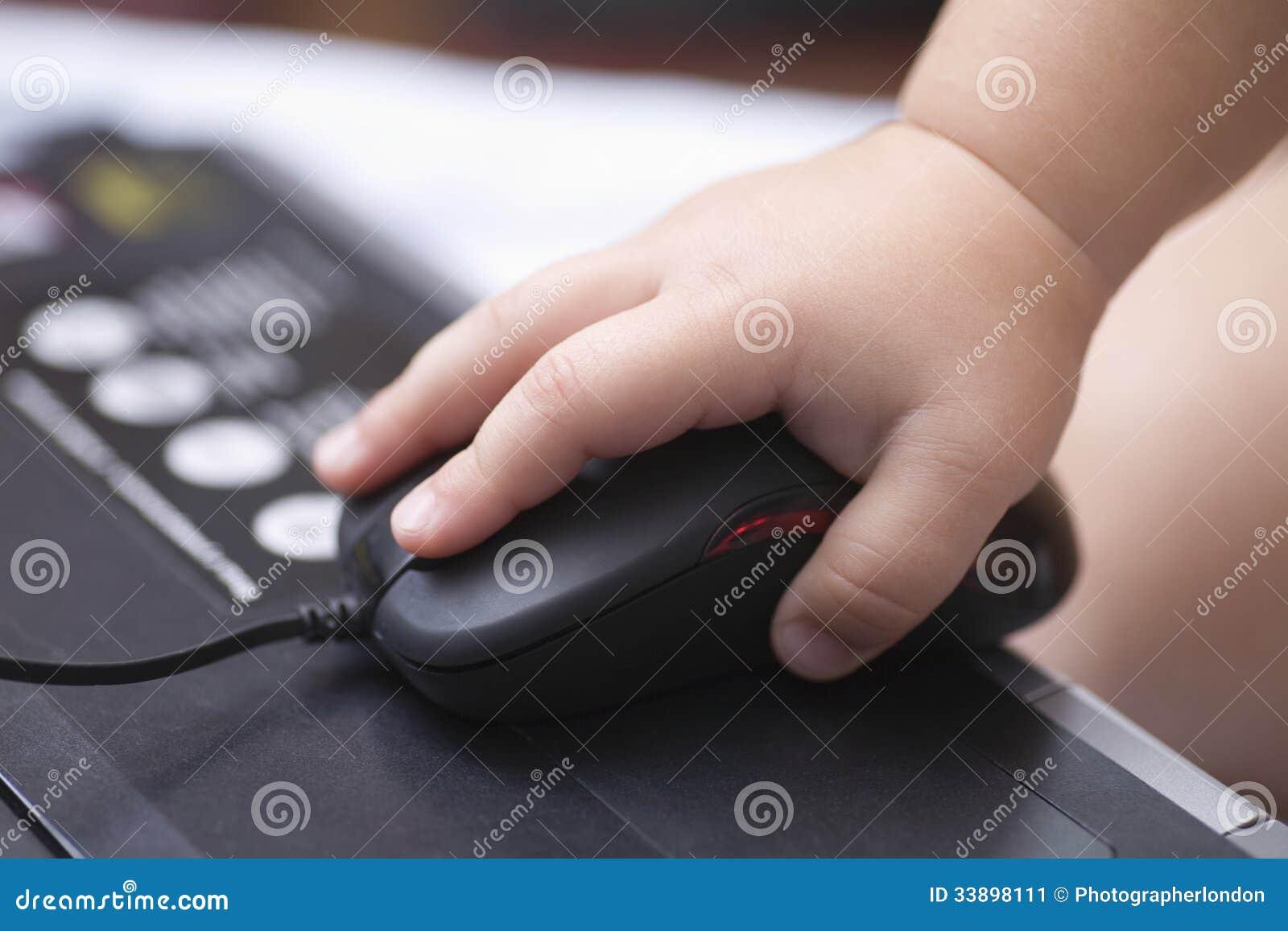 Χέρι μωρού που χρησιμοποιεί το ποντίκι υπολογιστών