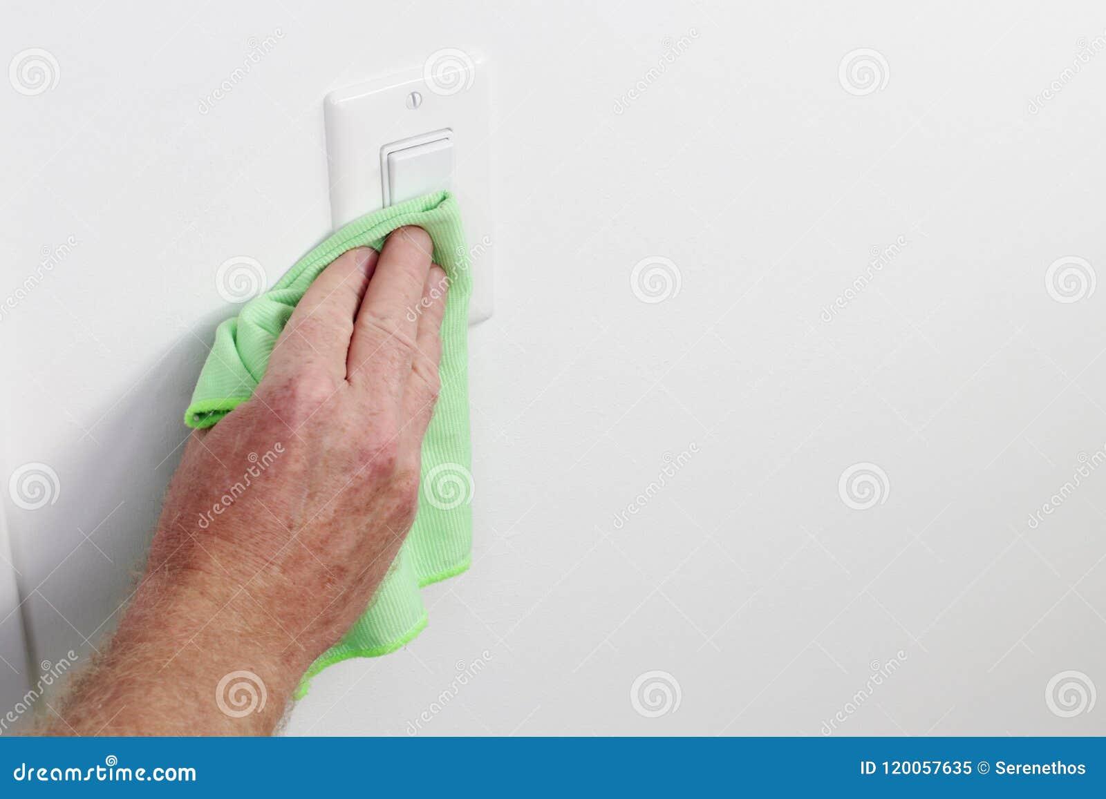 Χέρι που καθαρίζει την ελαφριά επιτροπή διακοπτών με το πράσινο ύφασμα