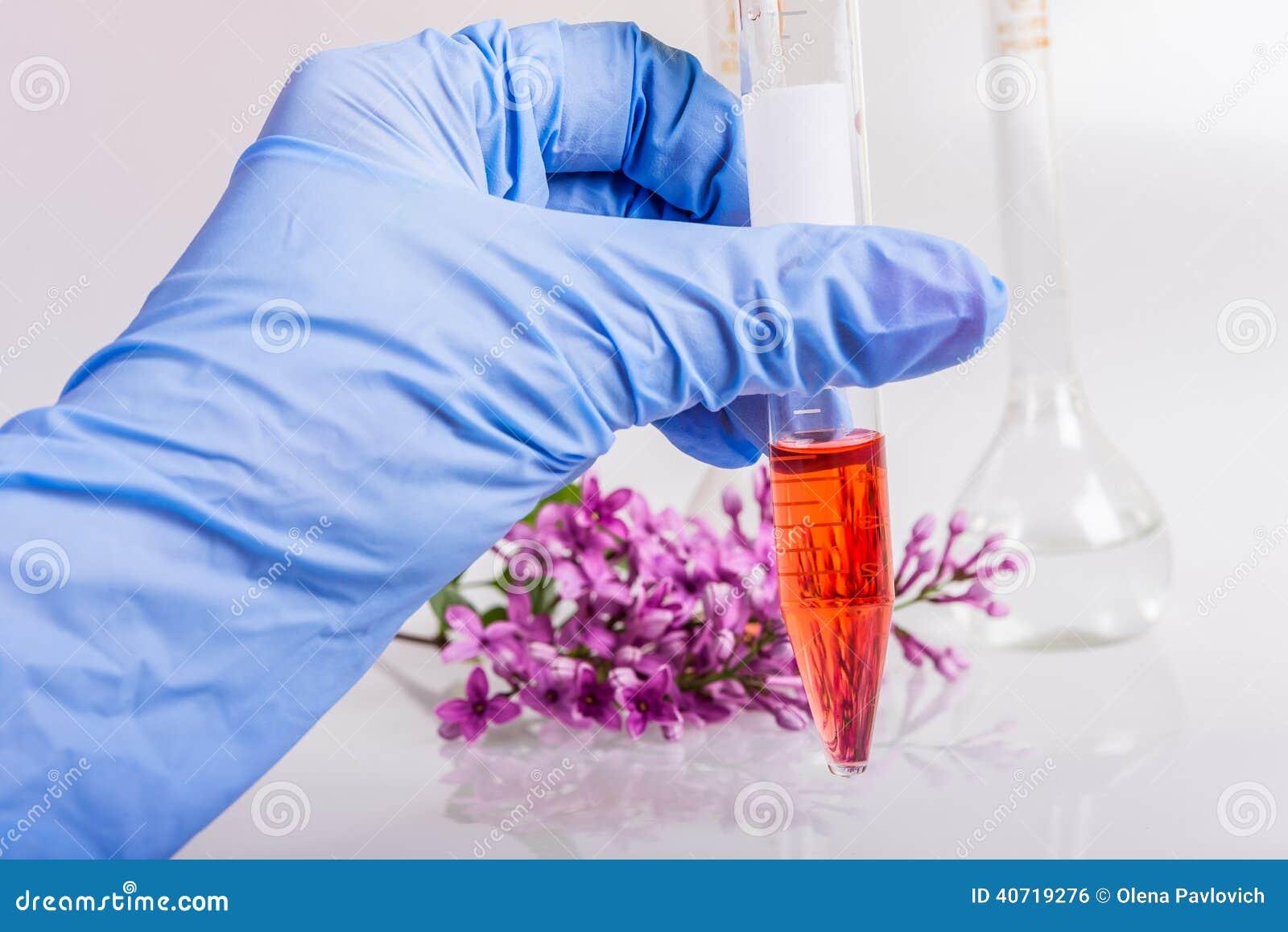 Χέρι που κρατά έναν σωλήνα με την εξαγωγή των φυσικών συστατικών στην αρωματοποιία