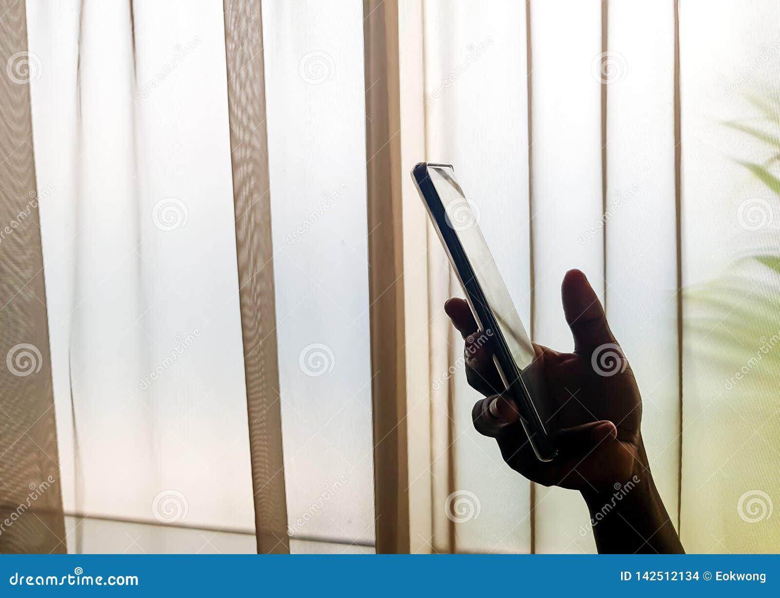 Χέρι προσώπου που κρατά ένα κινητό τηλέφωνο στο εσωτερικό, εκτός από ένα παράθυρο