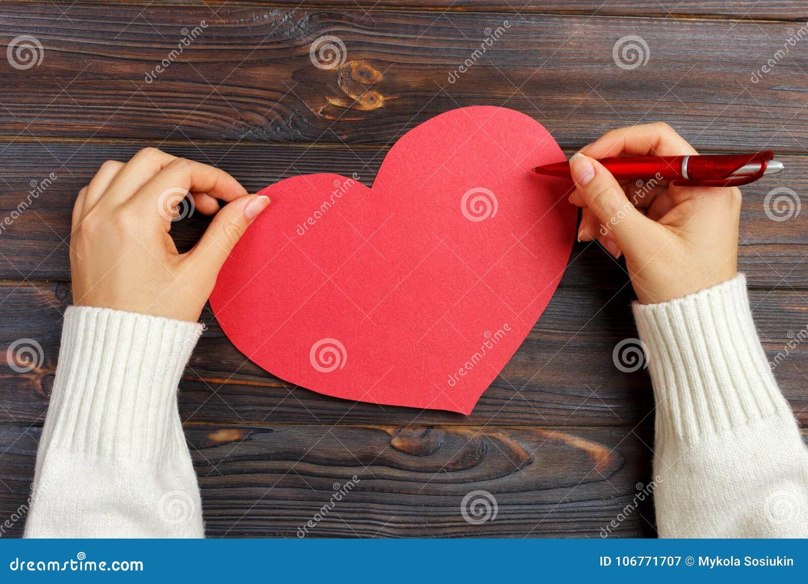 Χέρι της επιστολής αγάπης γραψίματος κοριτσιών την ημέρα βαλεντίνων Χειροποίητη κόκκινη κάρτα καρδιών Η γυναίκα γράφει στην κάρτα