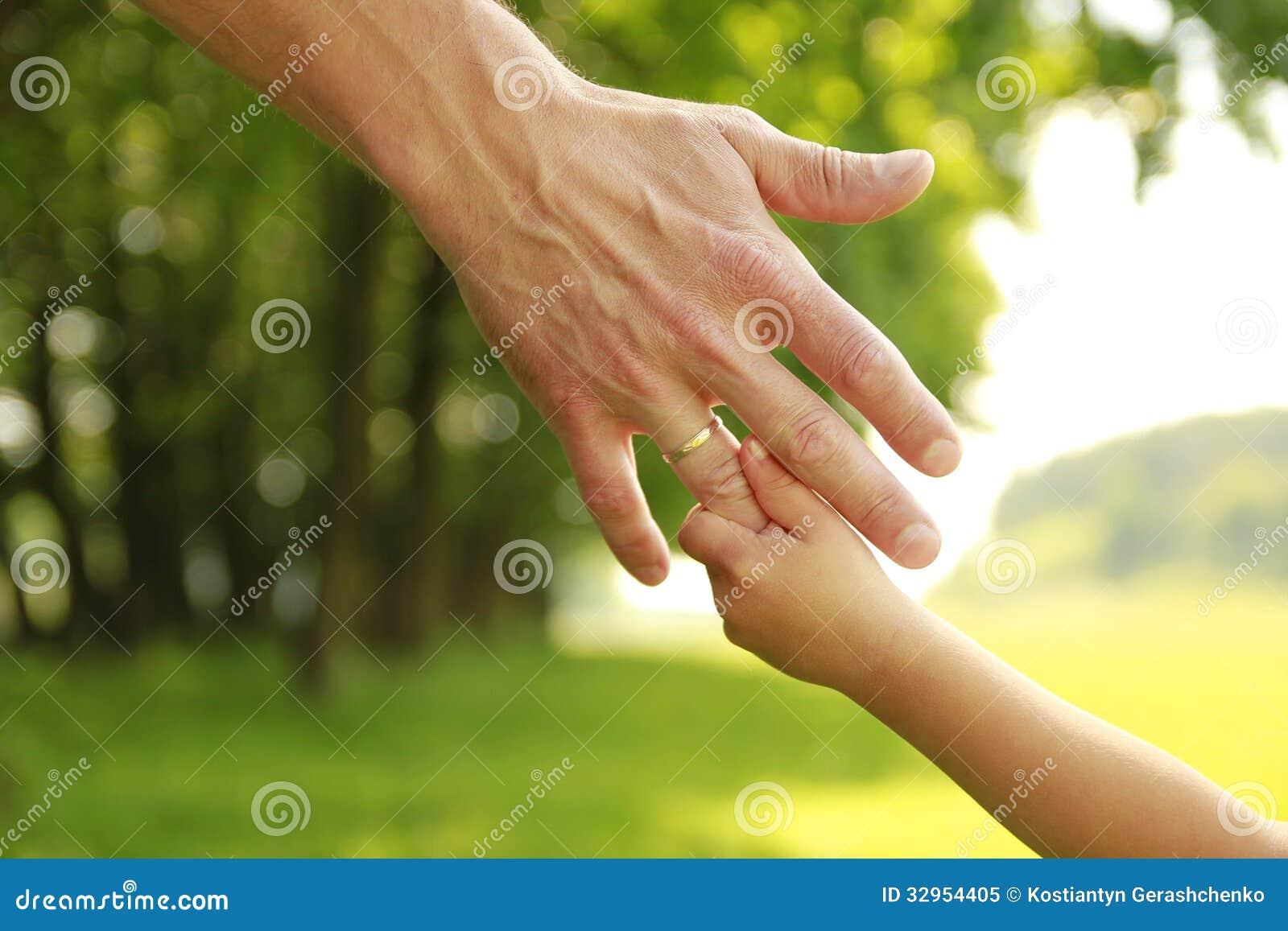Χέρι του γονέα και του παιδιού στη φύση