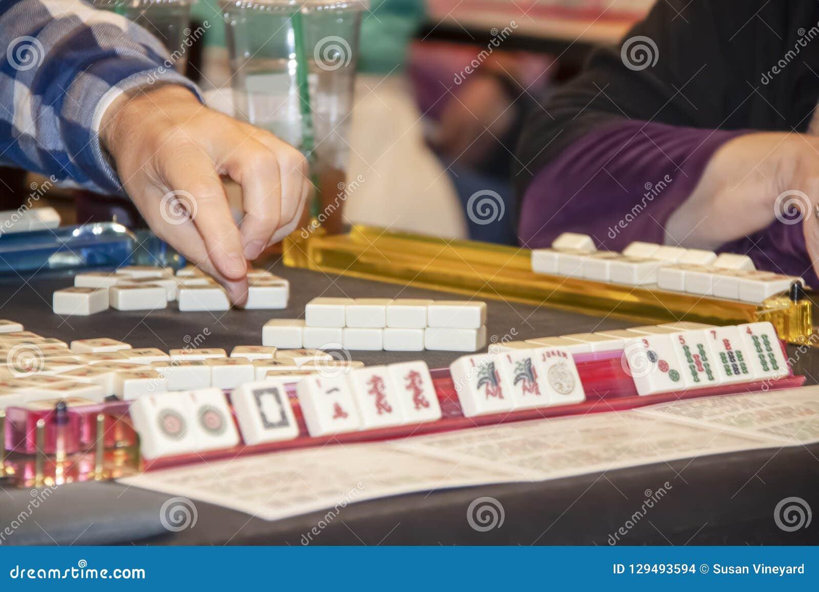 Χέρι του παίκτη που φθάνει για το κεραμίδι σε ένα παιχνίδι Mahjong - εκλεκτική εστίαση