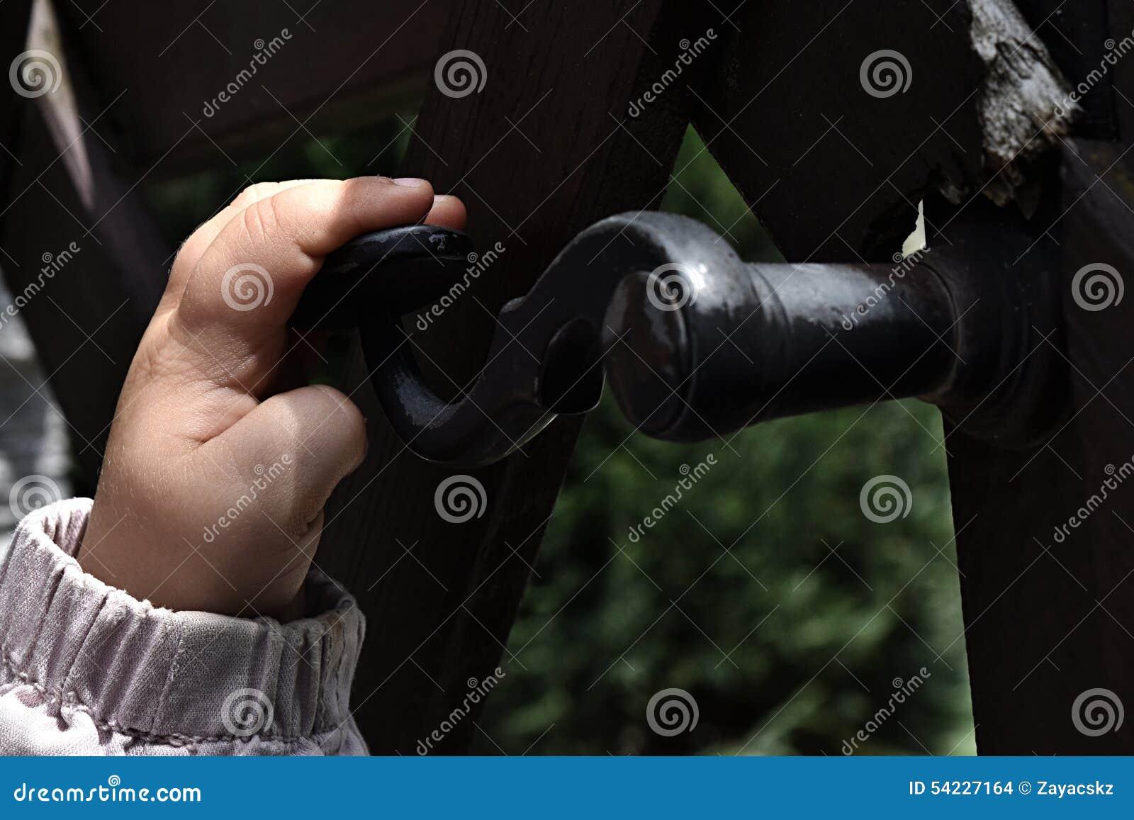 Χέρι χρονών της ανοίγοντας πόρτας κοριτσιών 3 με τη σφυρηλατημένη λαβή