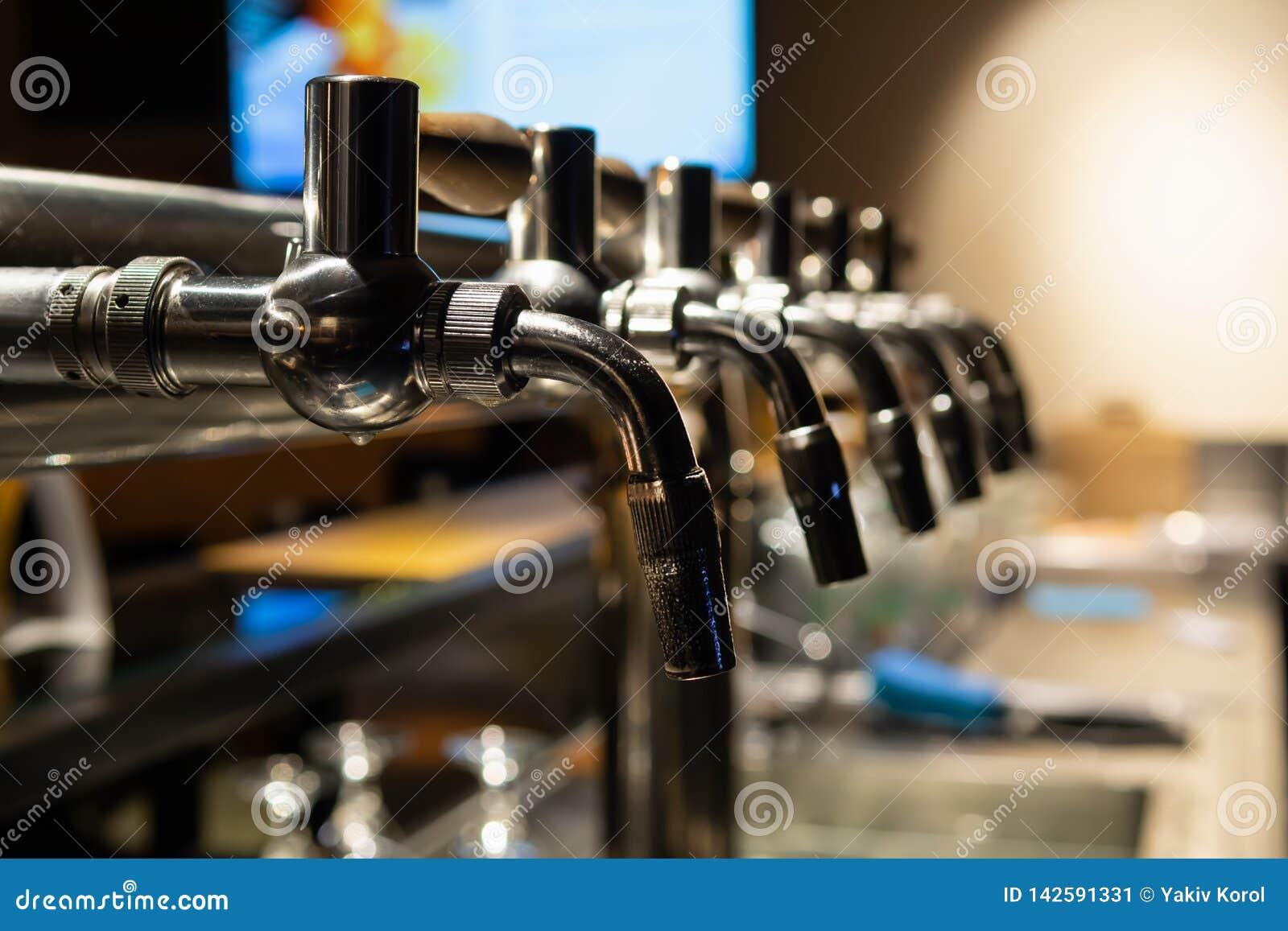 Χέρι bartender που χύνει μια μεγάλη μπύρα ξανθού γερμανικού ζύού στη βρύση Υπόλοιπο σε έναν φραγμό με τους φίλους