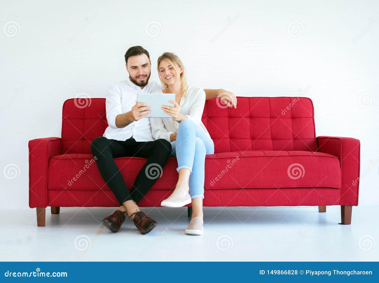 Χαλάρωση ζεύγους σε έναν καναπέ και να φανεί κινηματογράφος on-line με την ταμπλέτα στο σπίτι μαζί, ευτυχής και χαμόγελο, έννοια